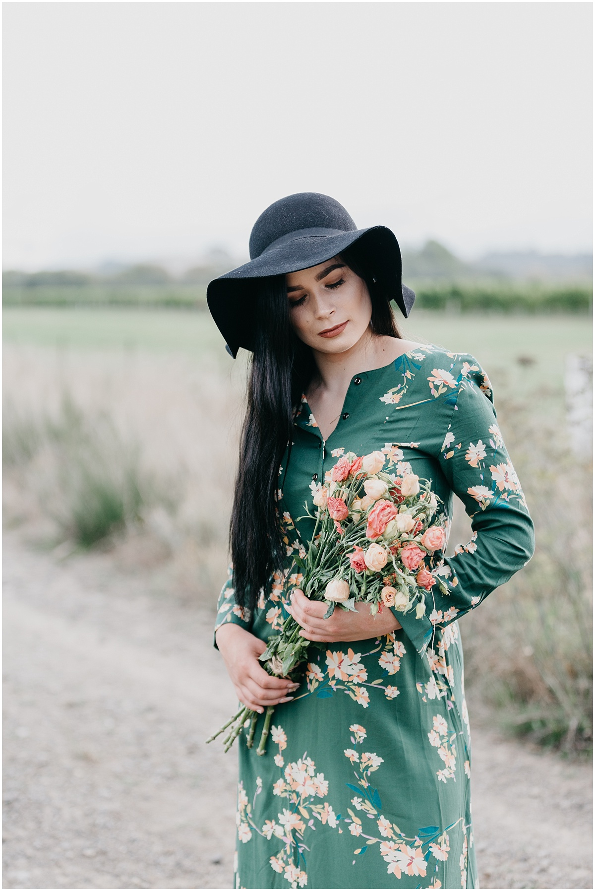 Woman long black hair in green dress looking at bouquet of wild flowers