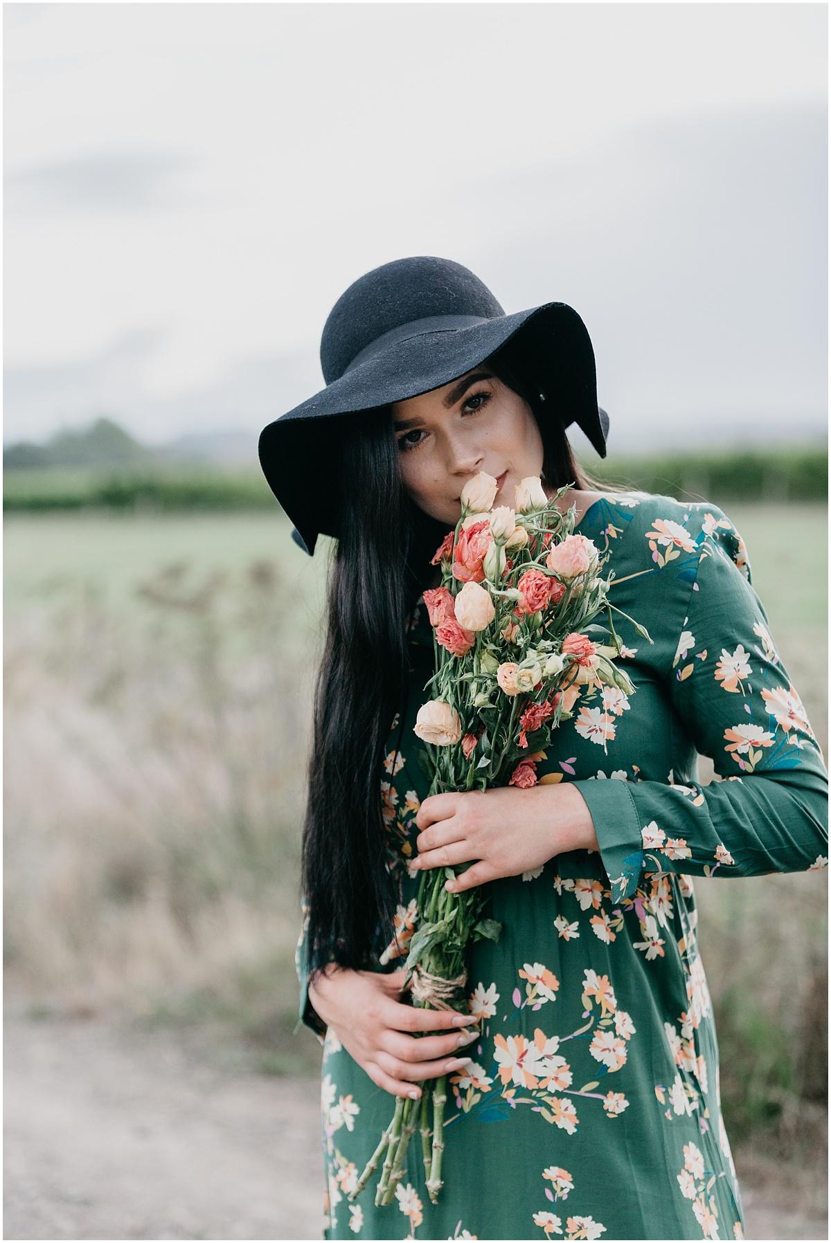 Woman in green dress smelling bouquet of flowers