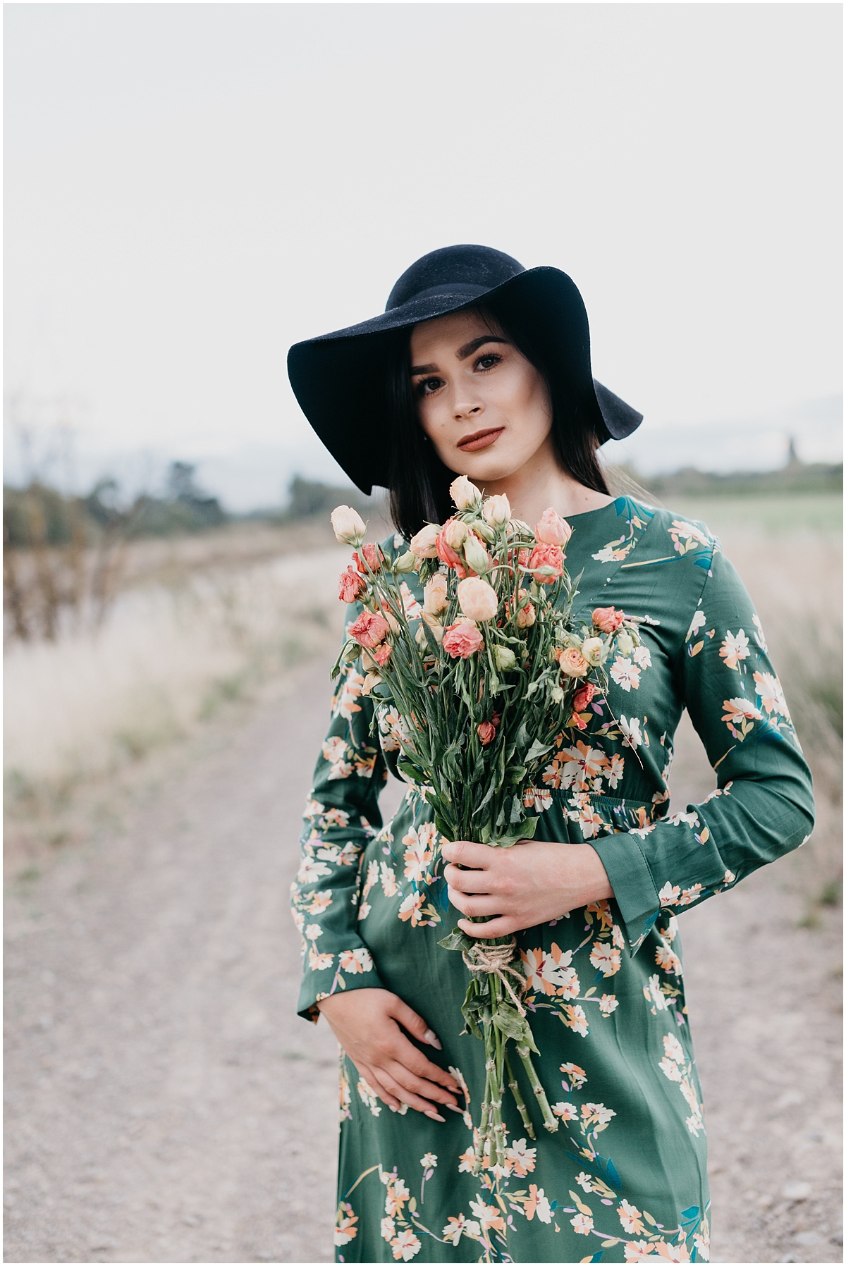 Woman in a green floral dress standing on a track