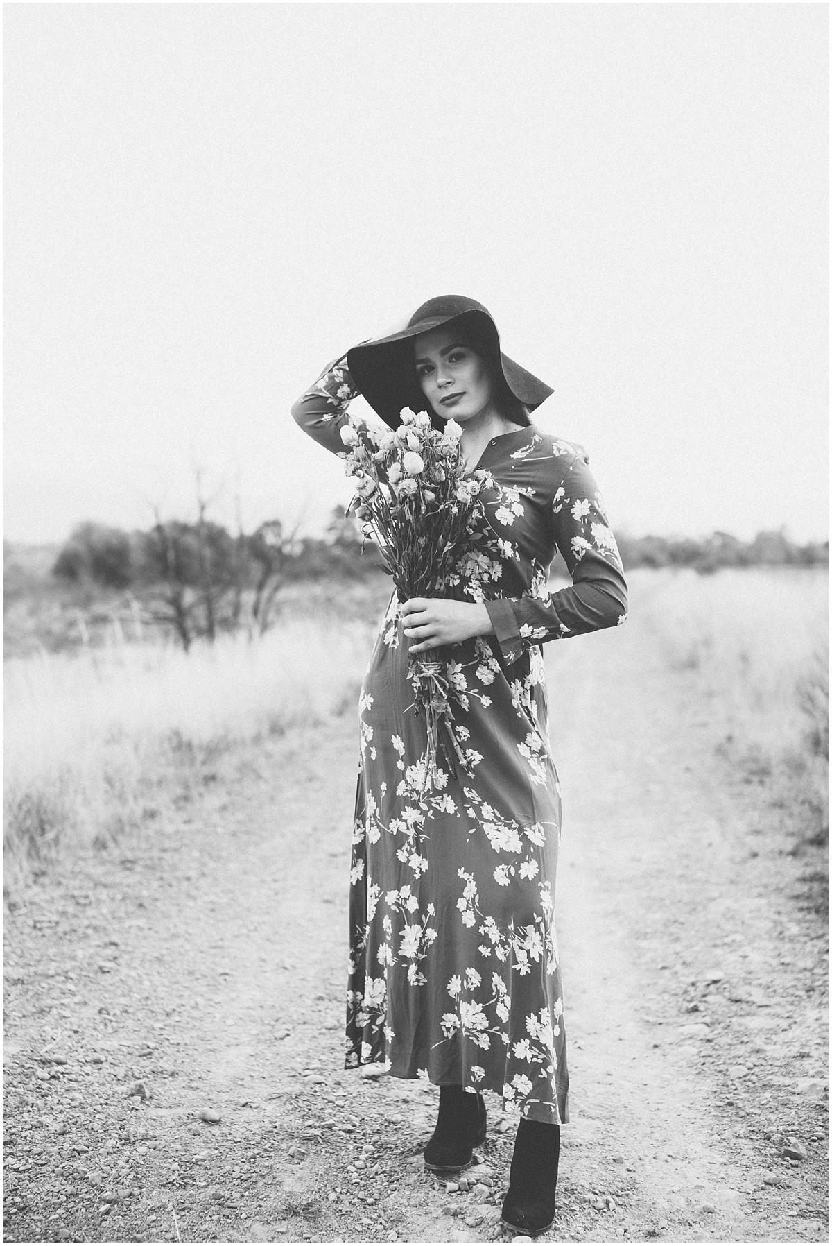 black and white photo of woman standing holding hat on head