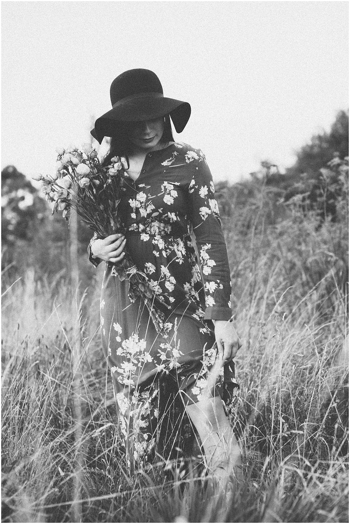 Black & White photo of girl in field with bouquet of flowers