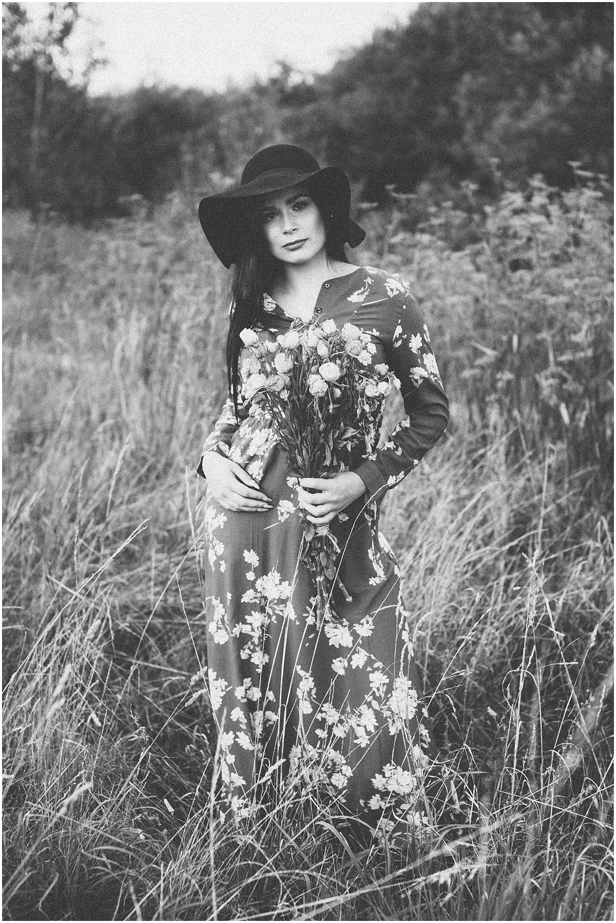 black & white photo of woam in a field of overgrown grass
