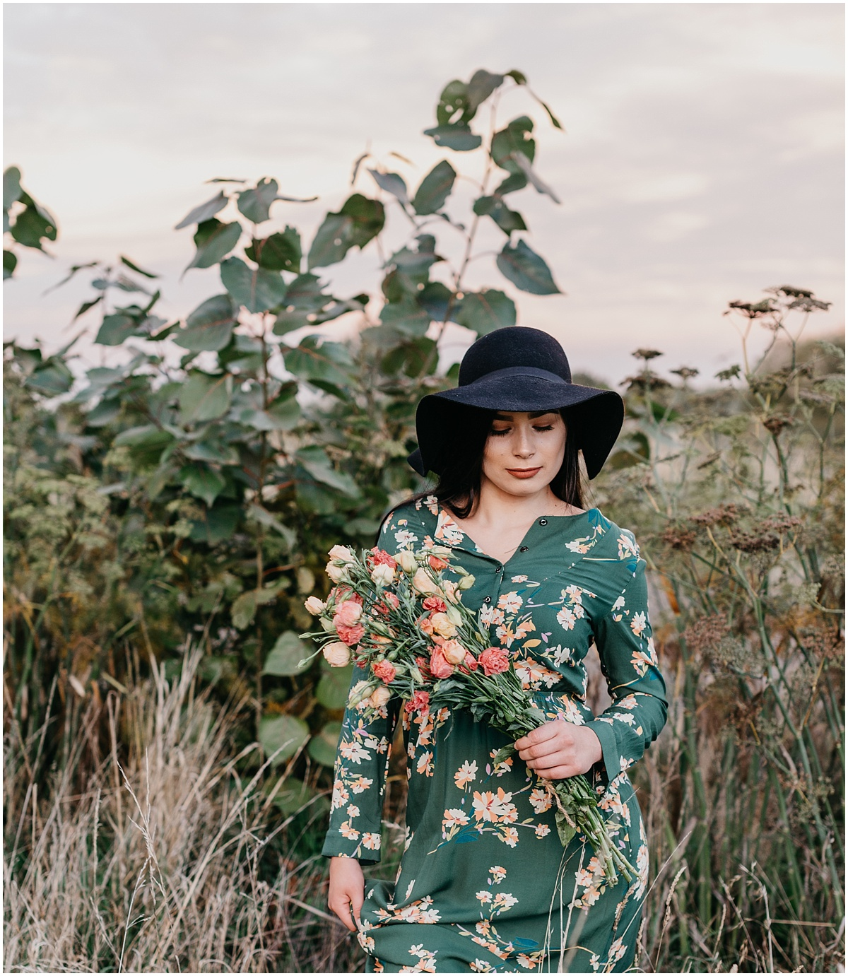 Woman in paddock wearing floral dress holding flowers a