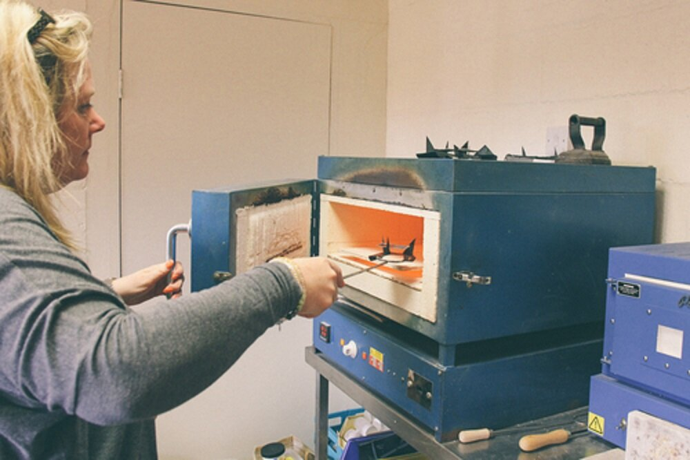 Teresa putting a picture into the kiln to fire.