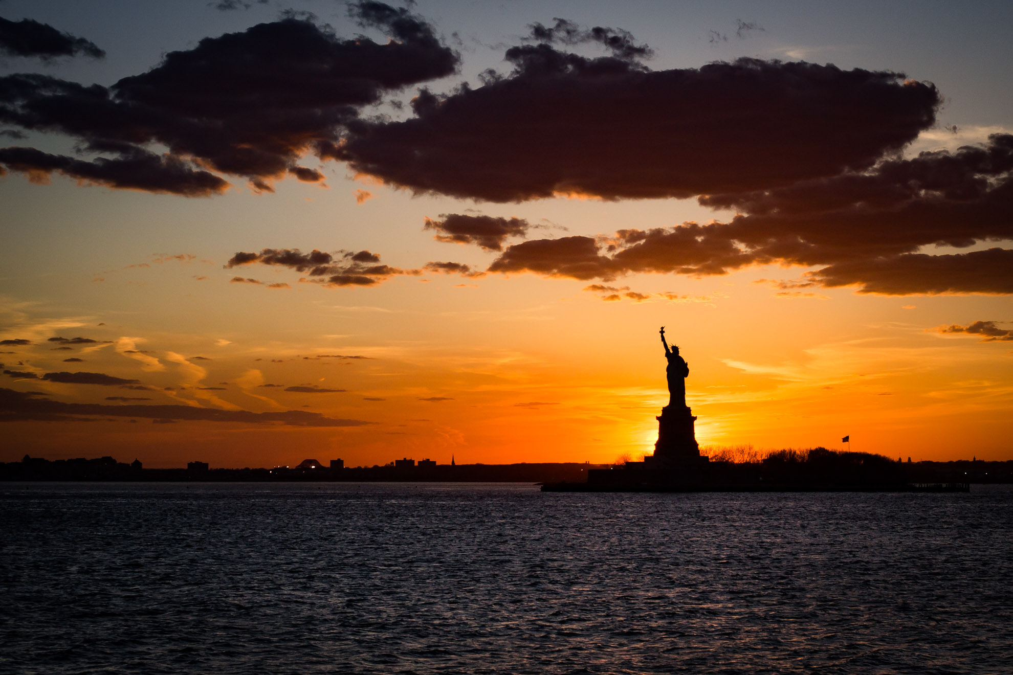 Sunset behind the statue of liberty