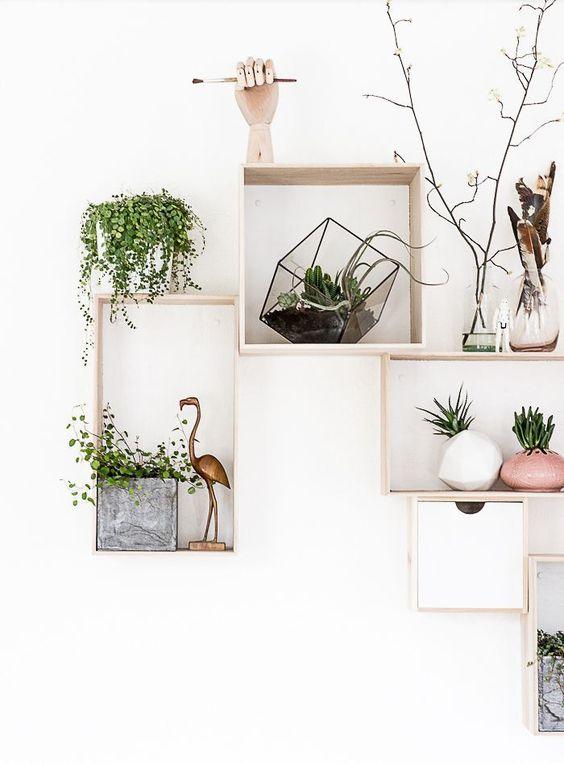 Een accentmuur: een rooster van hout met allerlei speelse attributen zoals planten, bloempotjes,...