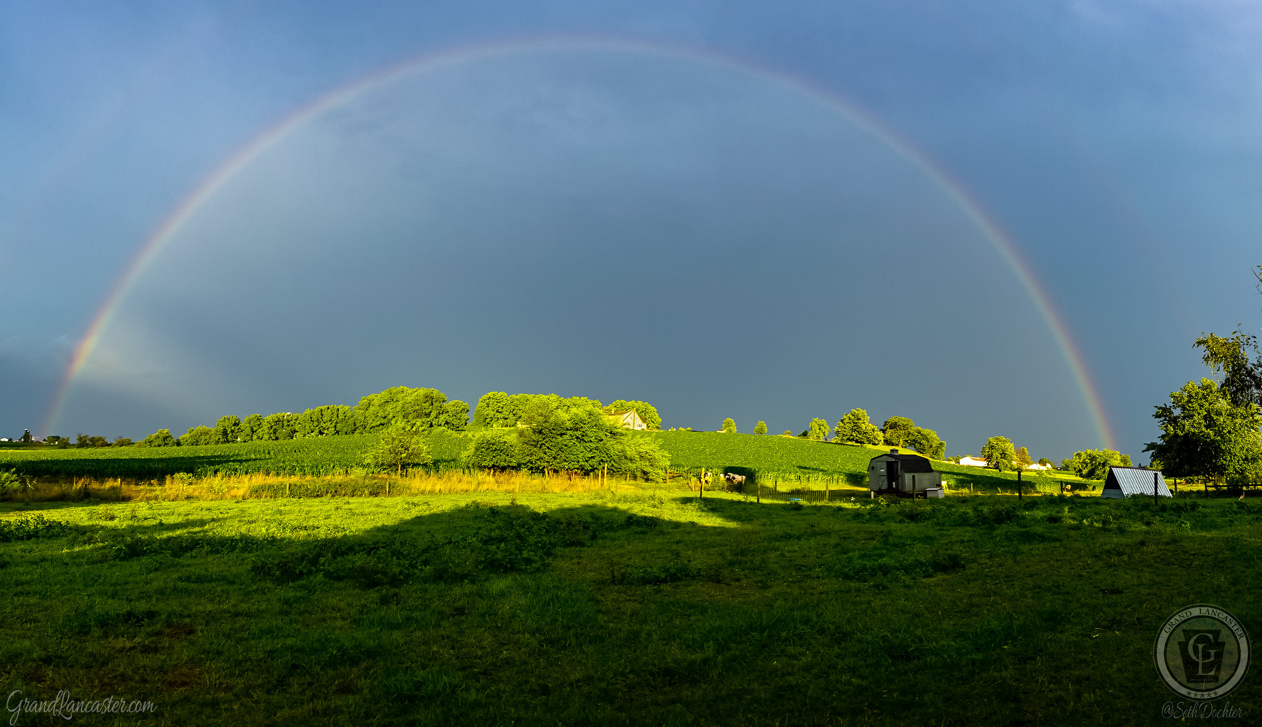 Within a few minutes, the clouds broke apart and the sky was filled with a massive arching rainbow. Honestly, when I look at this picture I like to pretend that farm to the left is shooting the rainbow across the sky. The second arch is very faint, but it was there as well.