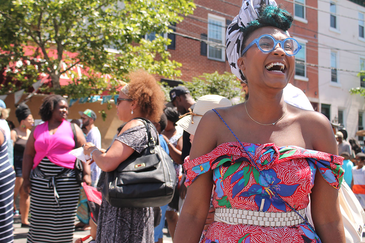 Rakia Reynolds, owner of Skai Blue Media, dons beautiful pastels and a contagious laugh at the Odunde Festival on South Street in Philadelphia, Pa. on Sunday June 12, 2016. Photography by Sofiya Ballin.