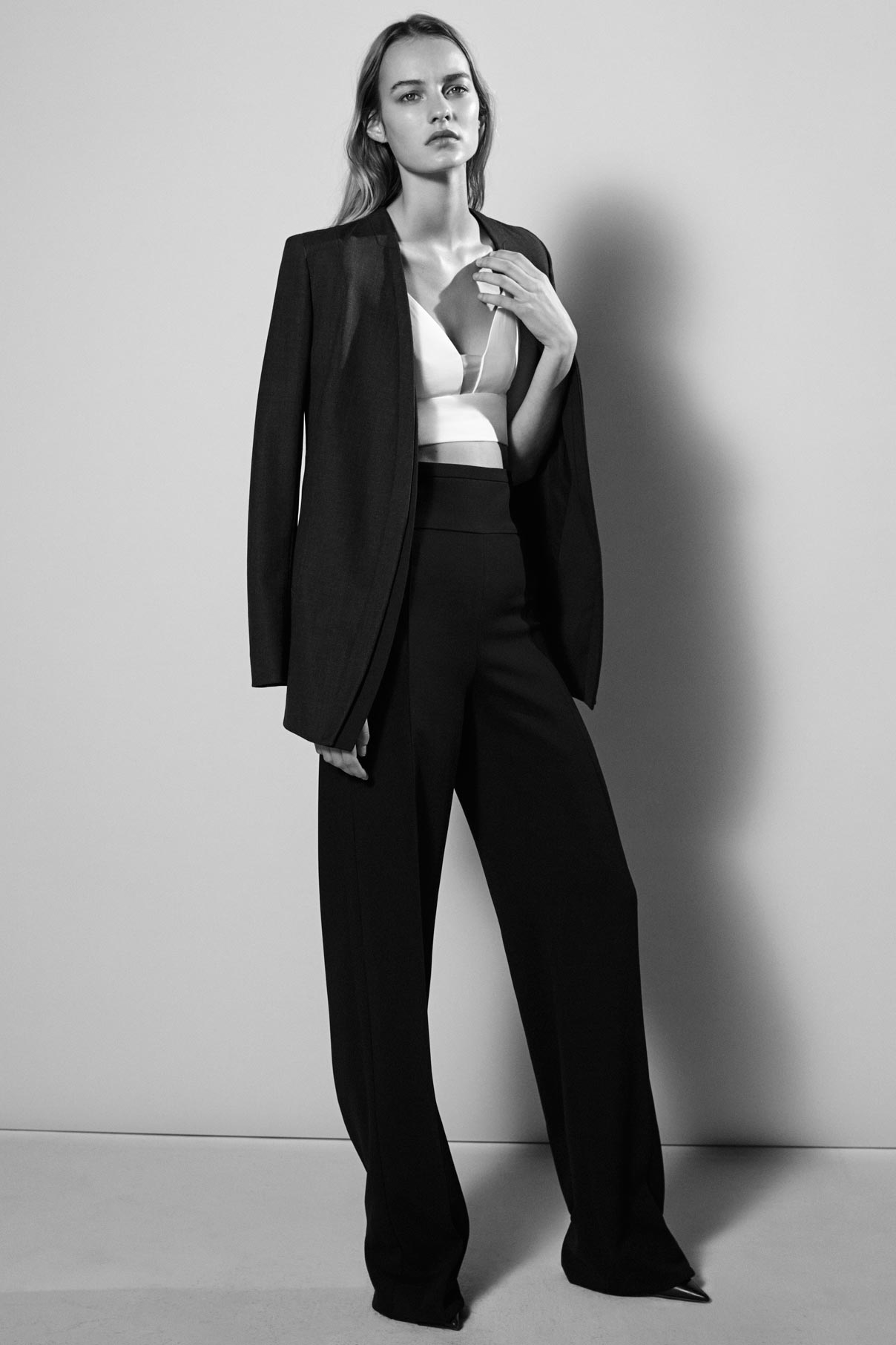 Look 11 Black wool gabardine jacket with white viscose crepe bra and black wool gabardine pant.