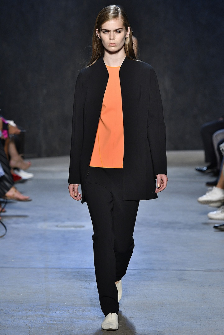 Narciso Rodriguez Spring 2017 collection. Black double knit zip jacket over safety orange double constructed wool top with black double knit track pant.