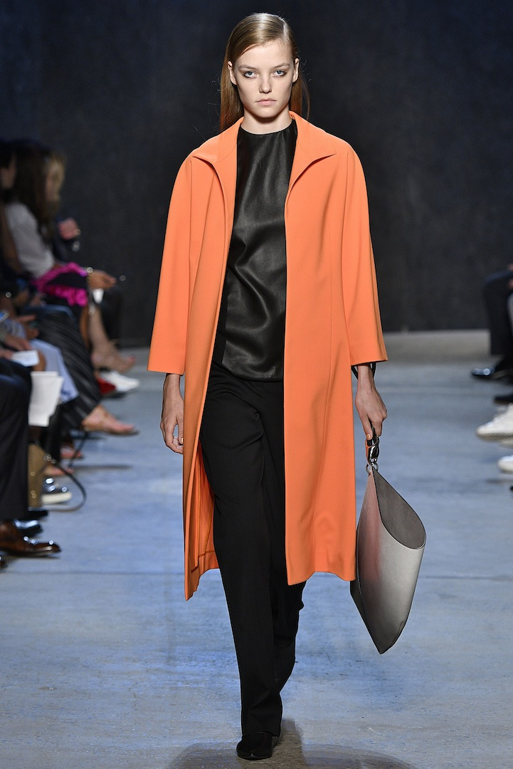 Narciso Rodriguez Spring 2017 collection. Safety orange double constructed wool coat over black mud silk tank with black double constructed wool trouser.