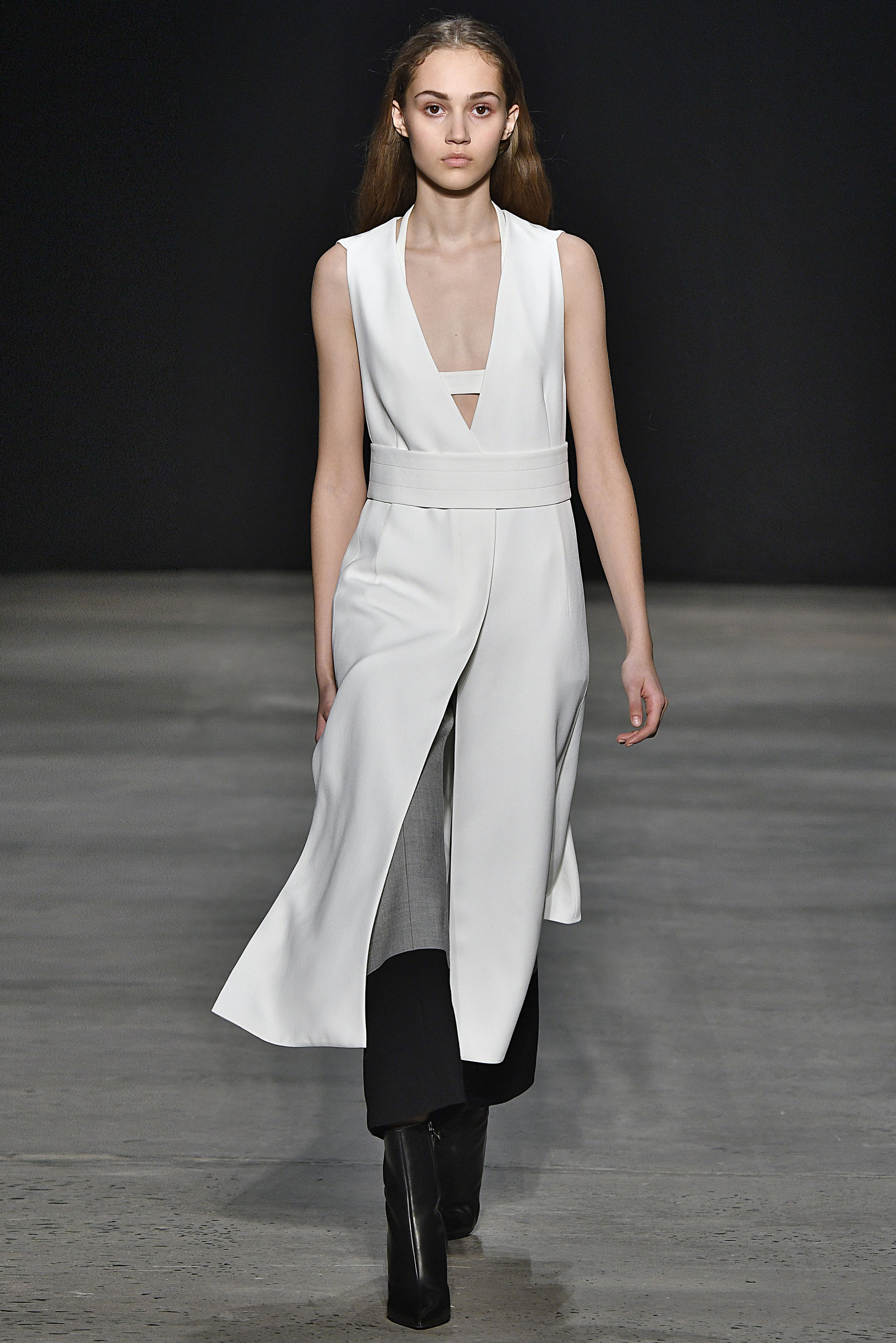 Narciso Rodriguez Fall 2017 collection. White twill crepe vest dress over white silk sling bra with grey/black engineered stripe pant.