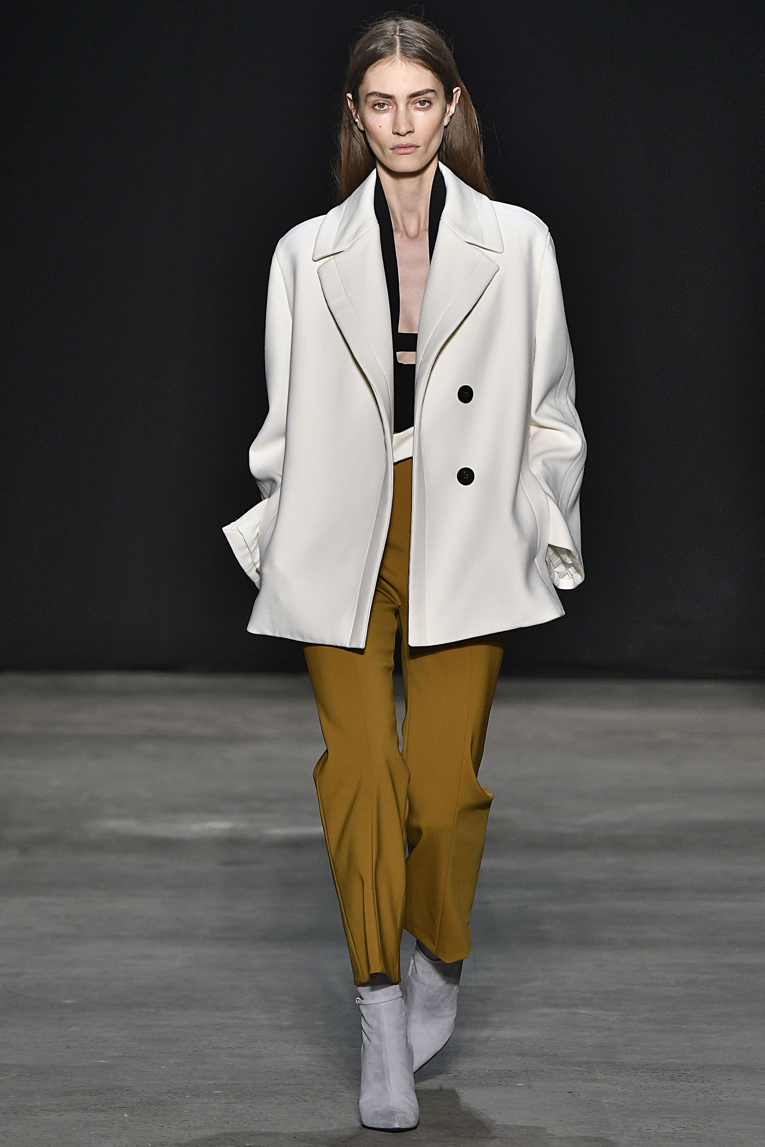 Narciso Rodriguez Fall 2017 collection. Ivory wool twill tab peacoat over black double knit halter and black silk sling bra with moss pressed wool pant.
