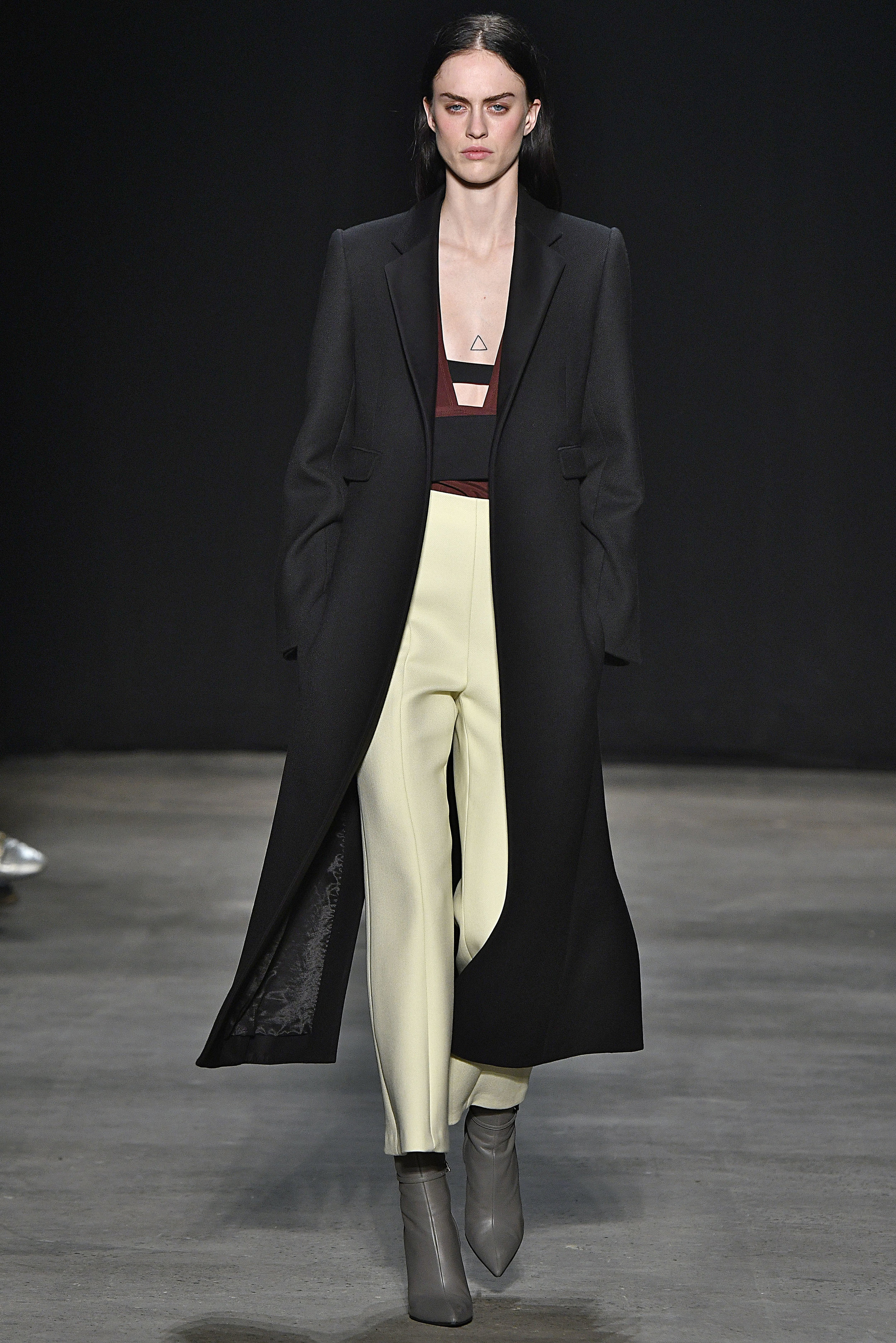 Narciso Rodriguez Fall 2017 collection. Black wool twill tab coat over claret silk crepe top with pale yellow wool twill pant.