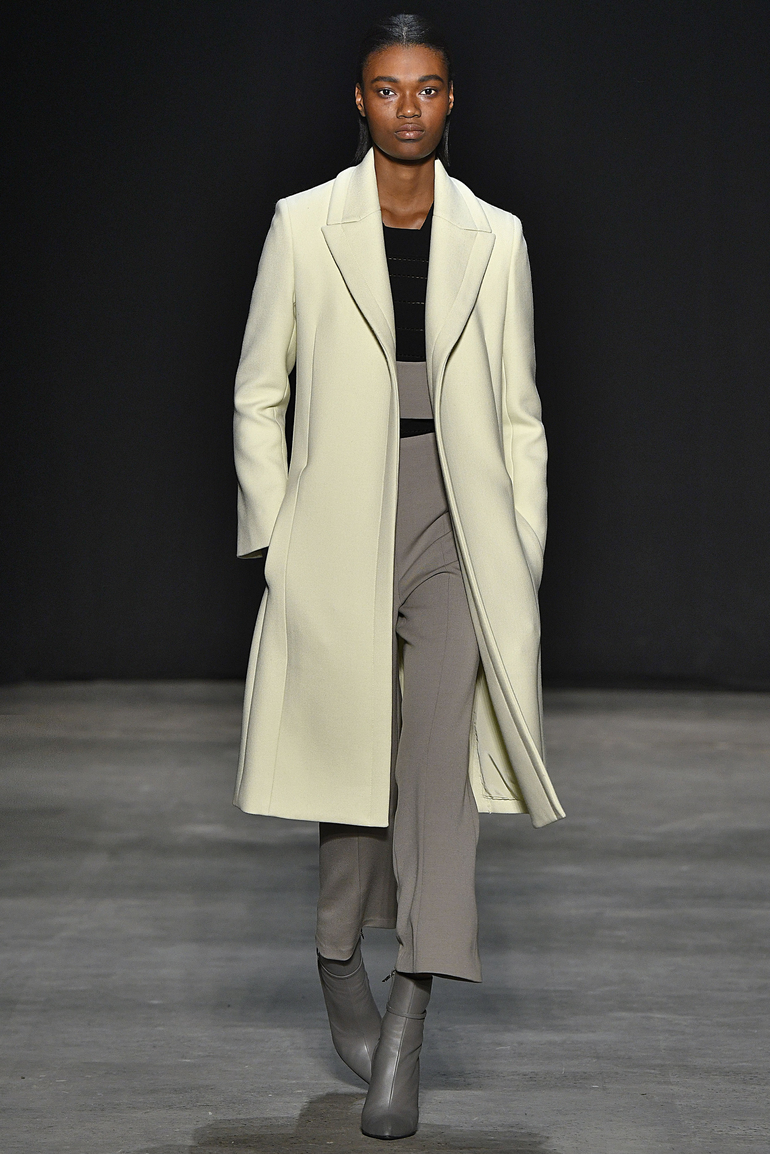Narciso Rodriguez Fall 2017 collection. Pale yellow wool twill tab coat over black knit top with khaki wool barathea pant.