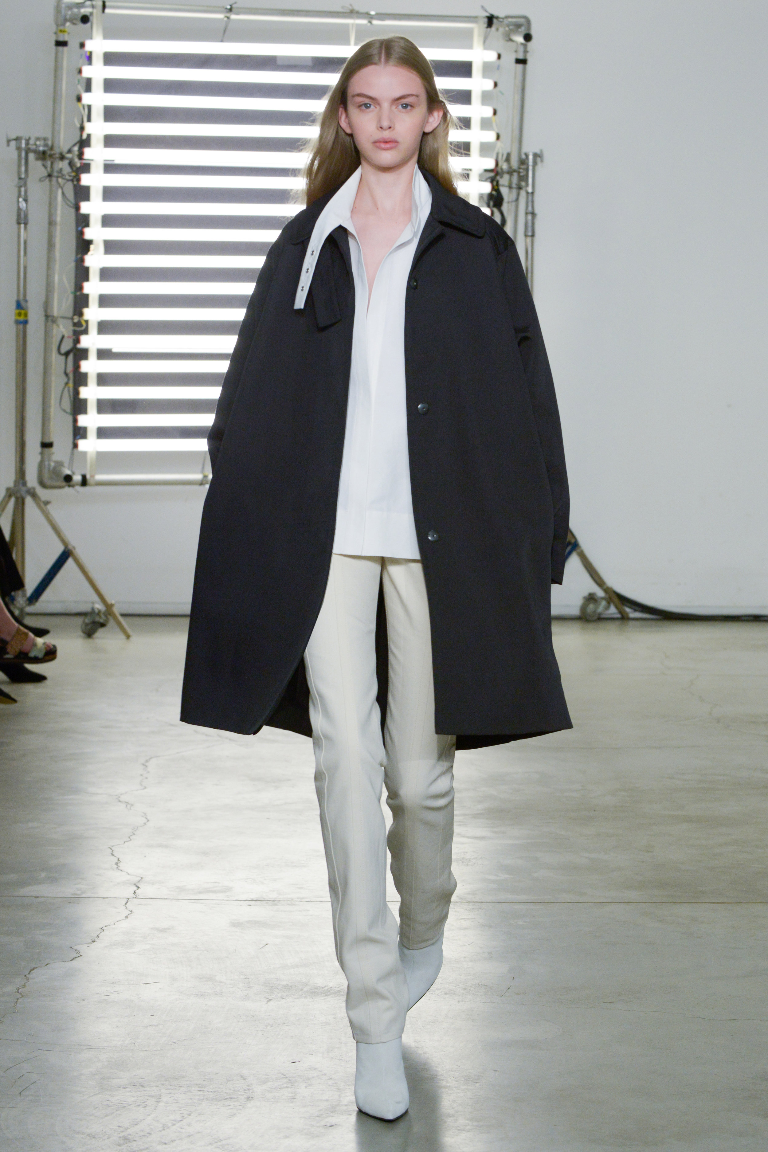 Look 12 Black wool/nylon canvas coat over white cotton/silk faille top with natural denim pant.