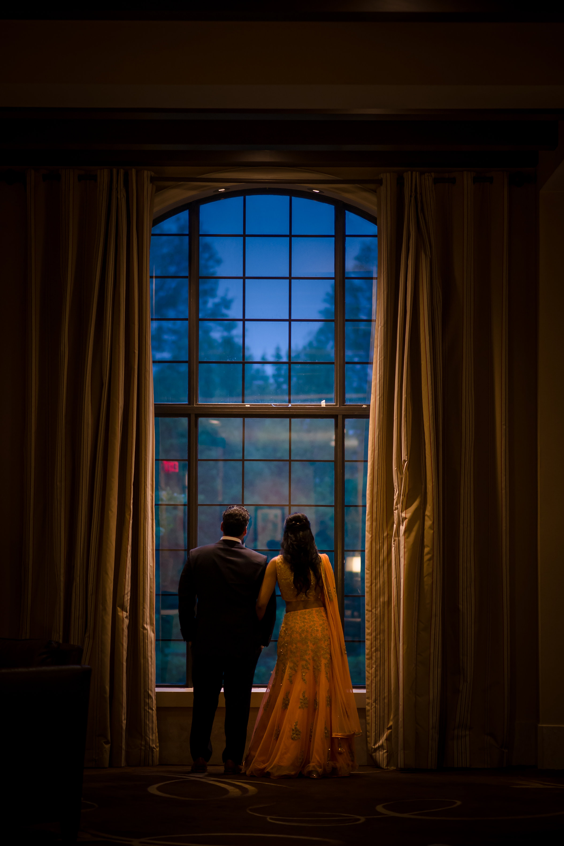 INDIAN COUPLE LOOKING OUT WINDOW