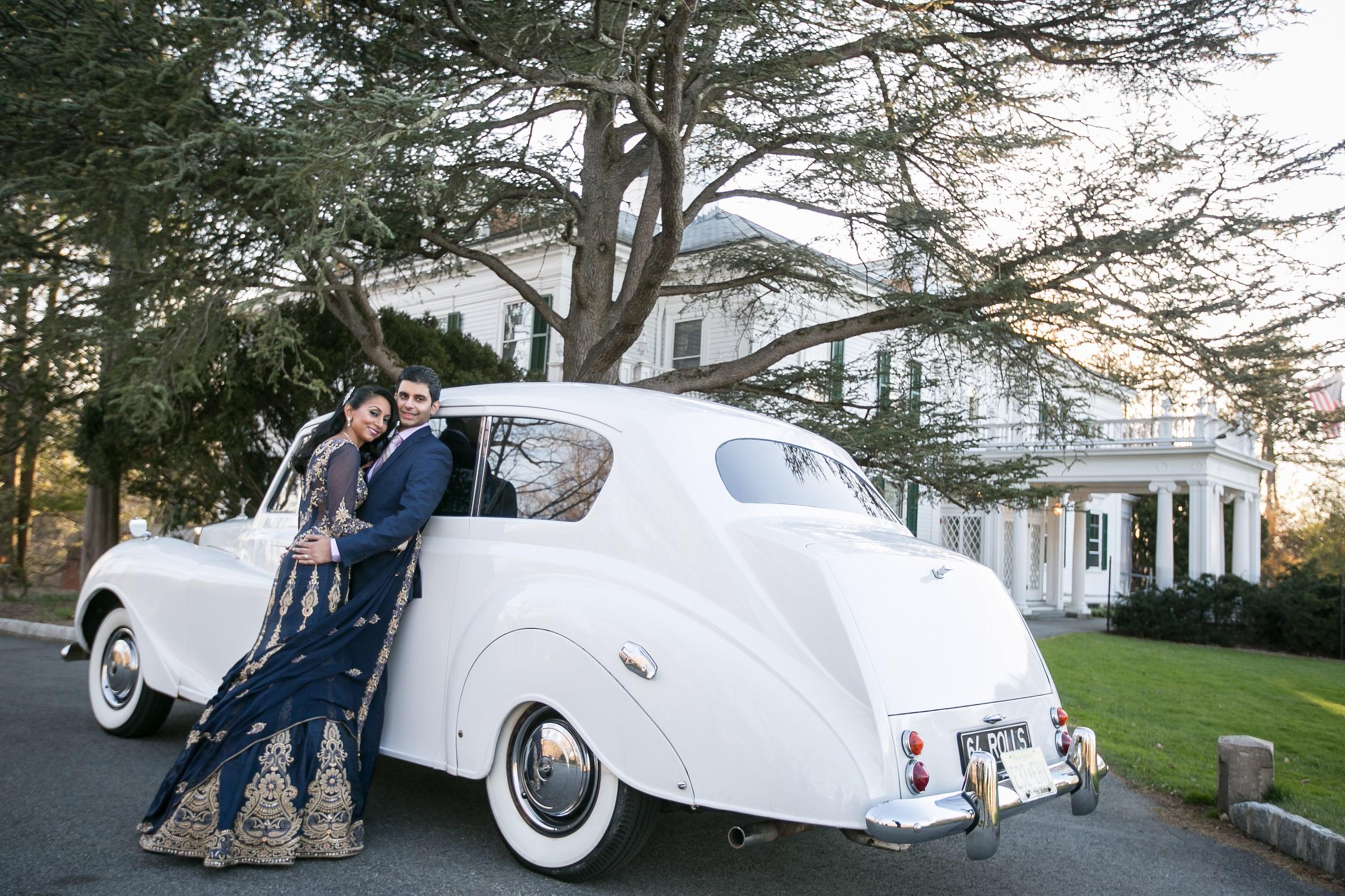 BRIDE AND GROOM ON VINTAGE CAR