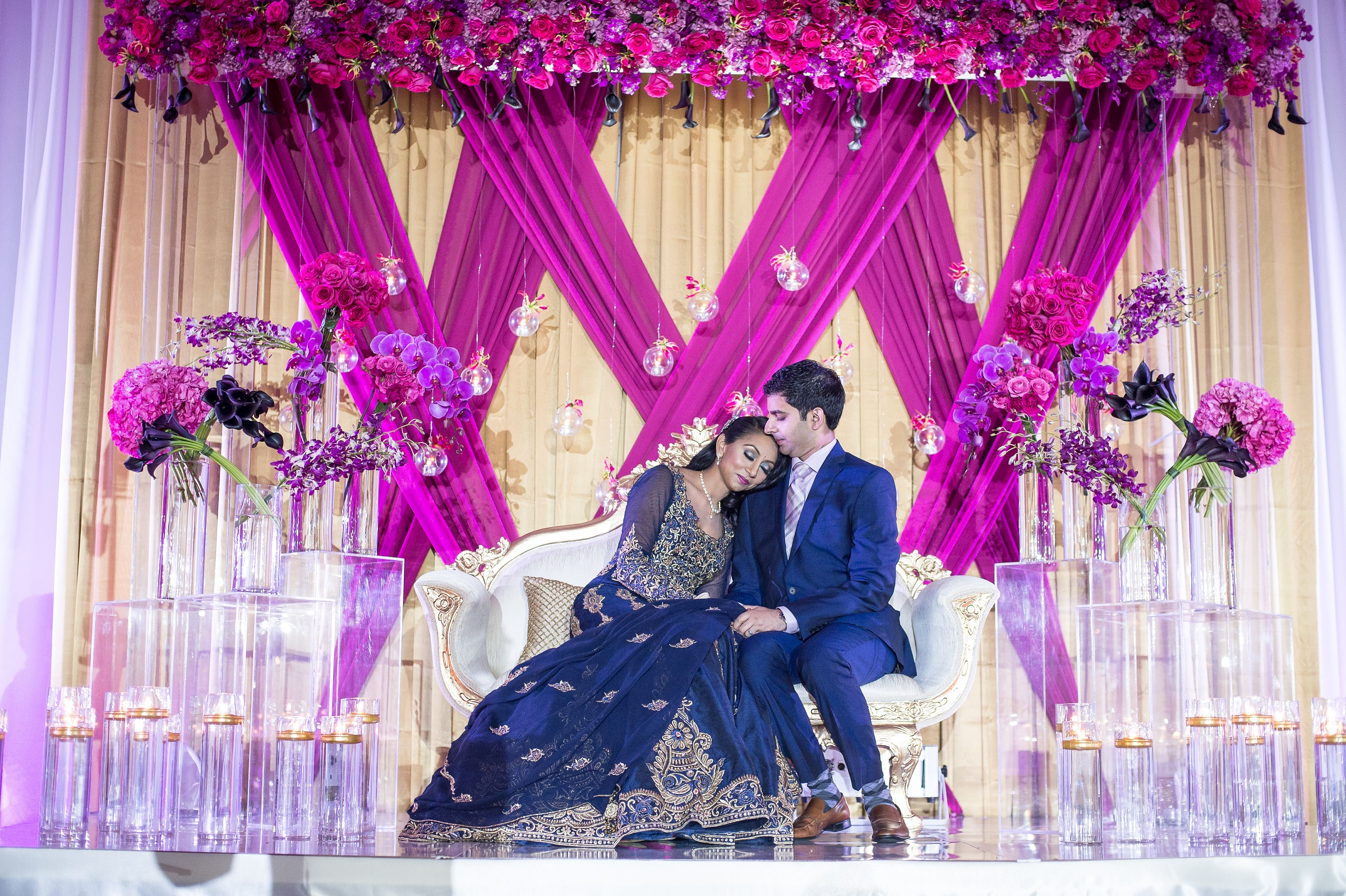 BRIDE LEANING ON GROOM IN FRONT OF BACKDROP