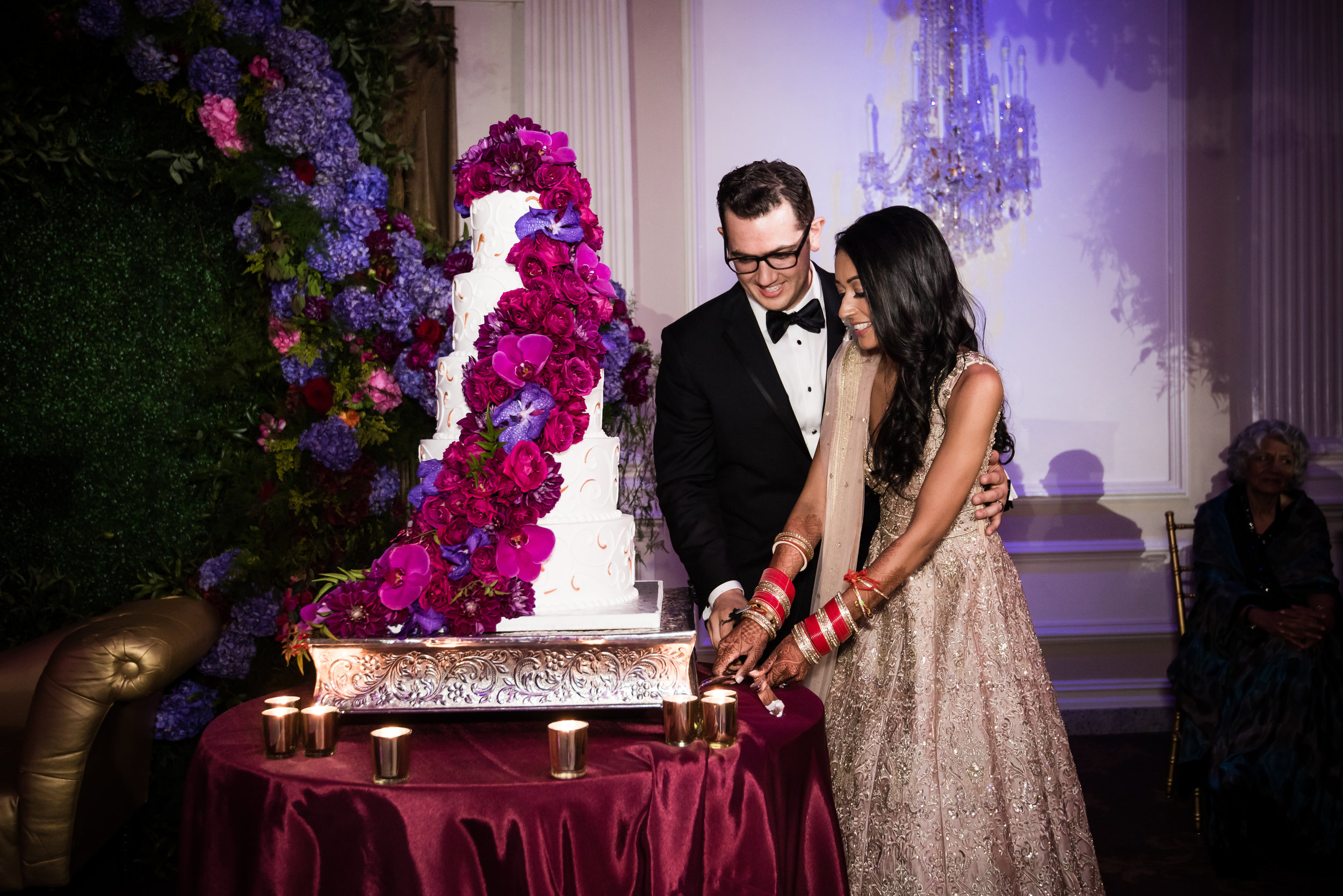 INDIAN WEDDING RECEPTION BRIDE AND GROOM CUTTING CAKE.jpg