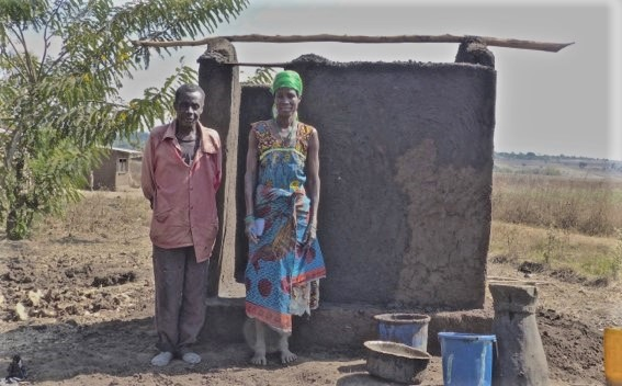 Margaret Manuel stands with her husband in front of their newly built latrine