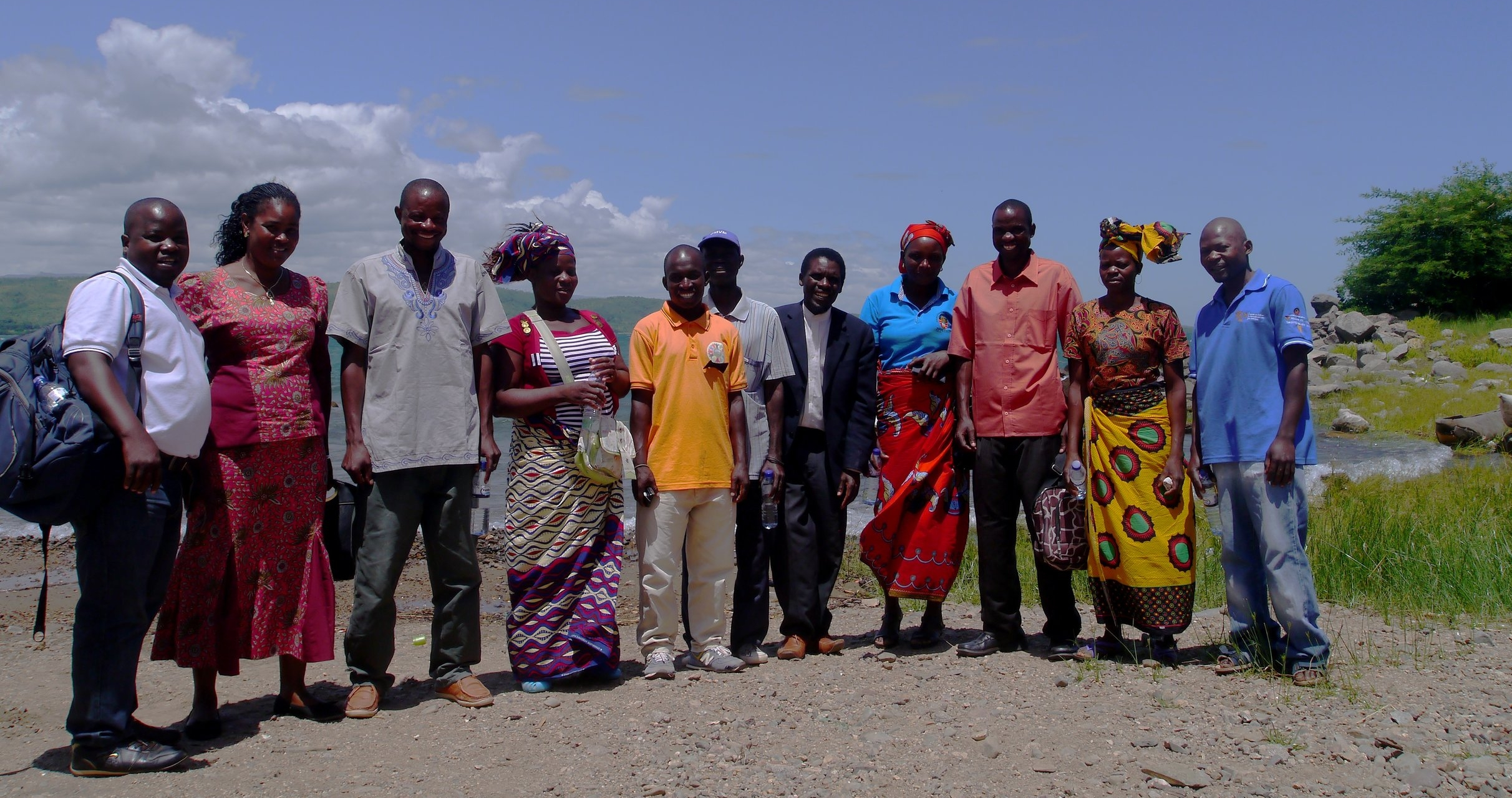 Maria (4th from right) with some members of the Metangula SAMCom on the shoreline of Lake Malawi.