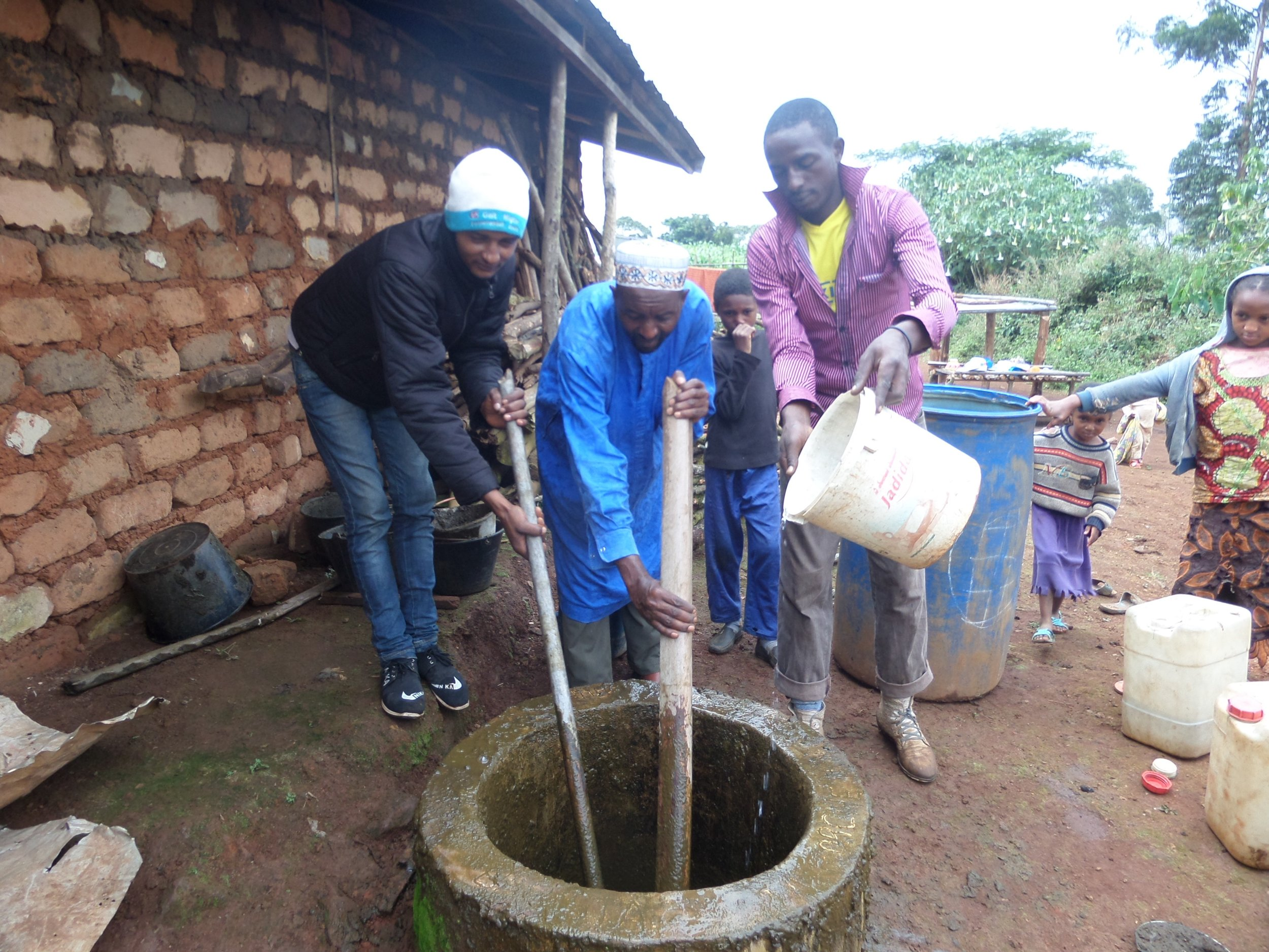 Alhadji (centre) tending to his biogas system. As president of his local Dialogue Platform, he also takes a central position in mediating disputes in his community.