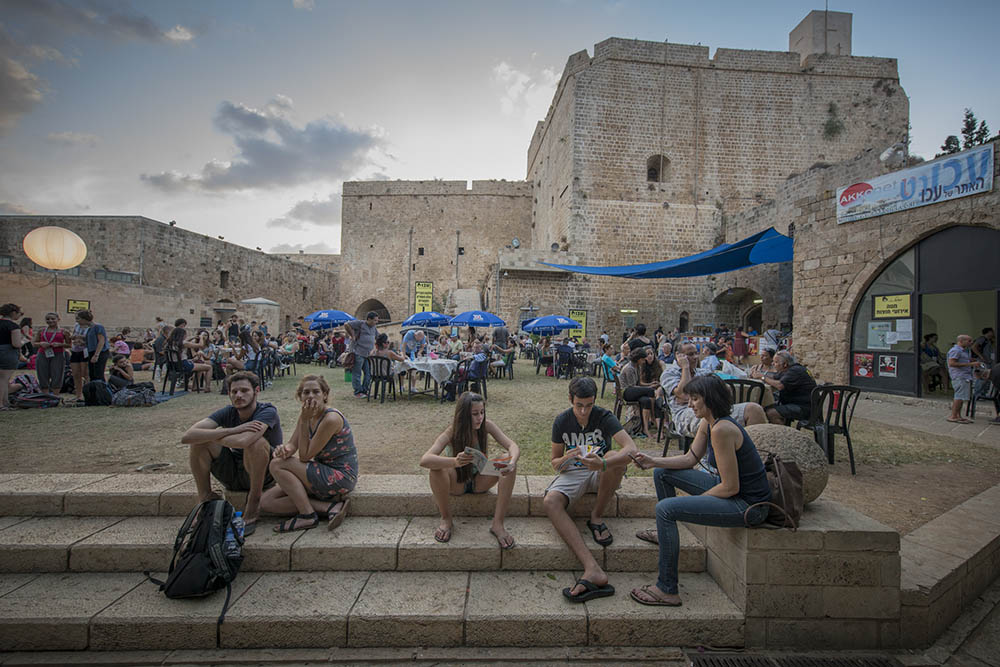 Crowds near a Crusader-period fortress during Akko's Festival of Alternative Israeli Theatre