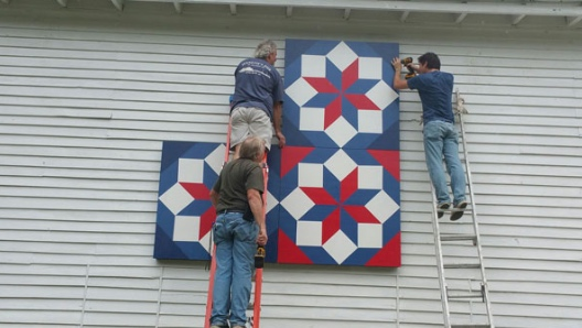 Securing the quilt to the barn.