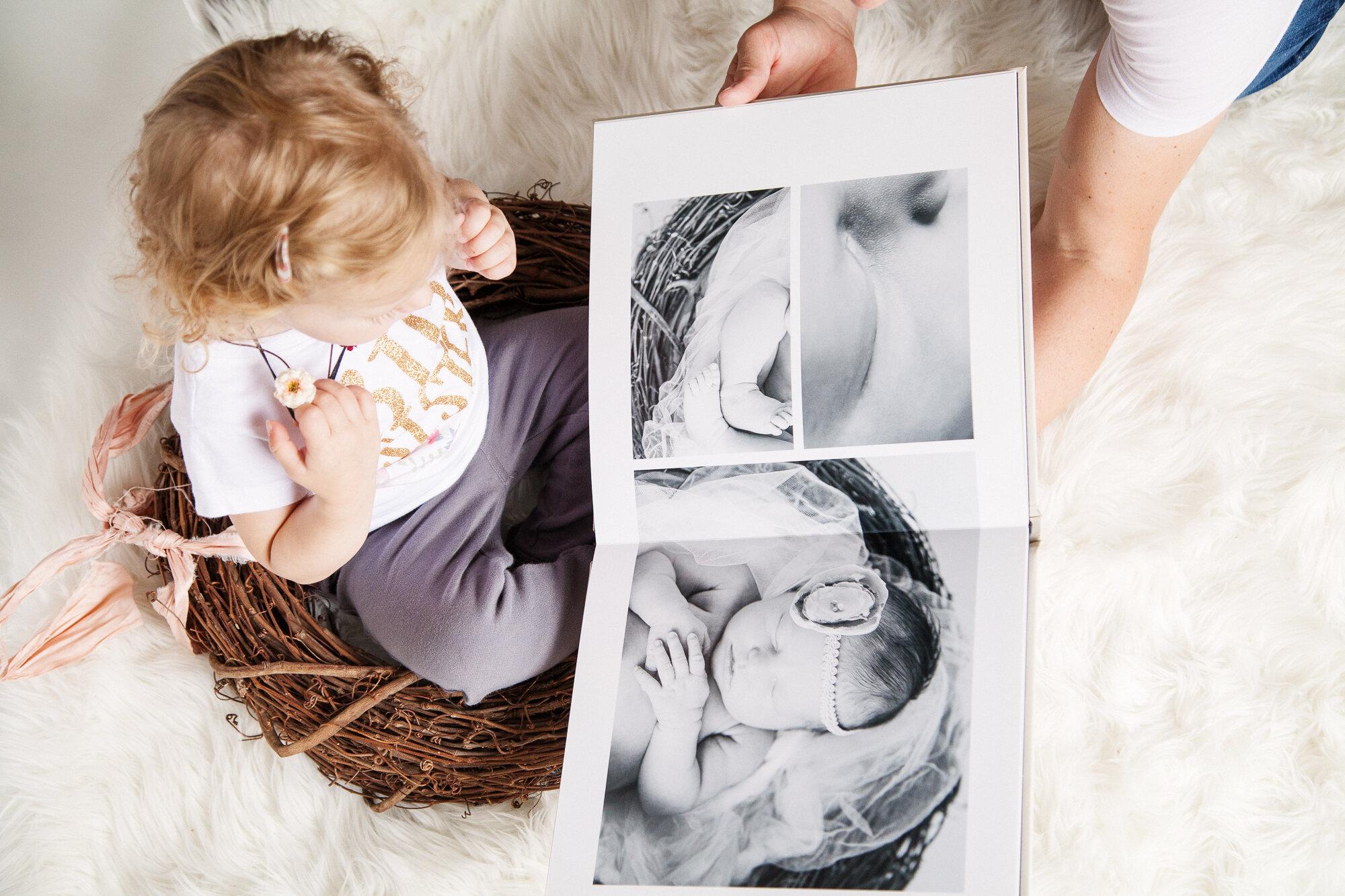 Toddler looking at newborn album