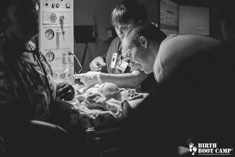 Dad looking at newborn baby on hospital warming table