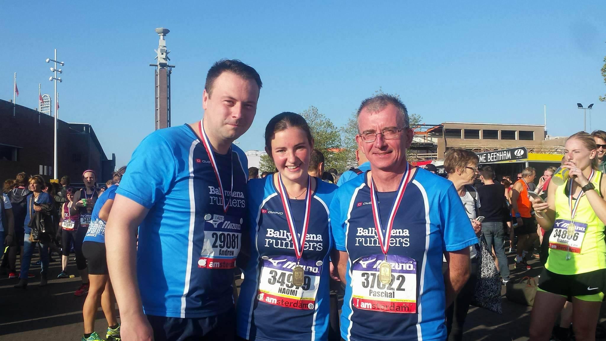 Andrew Hutchinson, Naomi Hutchinson and Paschal O'Sullivan proudly display their Amsterdam Half Marathon medals