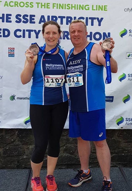 Lynsey McKeown and Adrian Dodds proudly display their Walled City Marathon medals