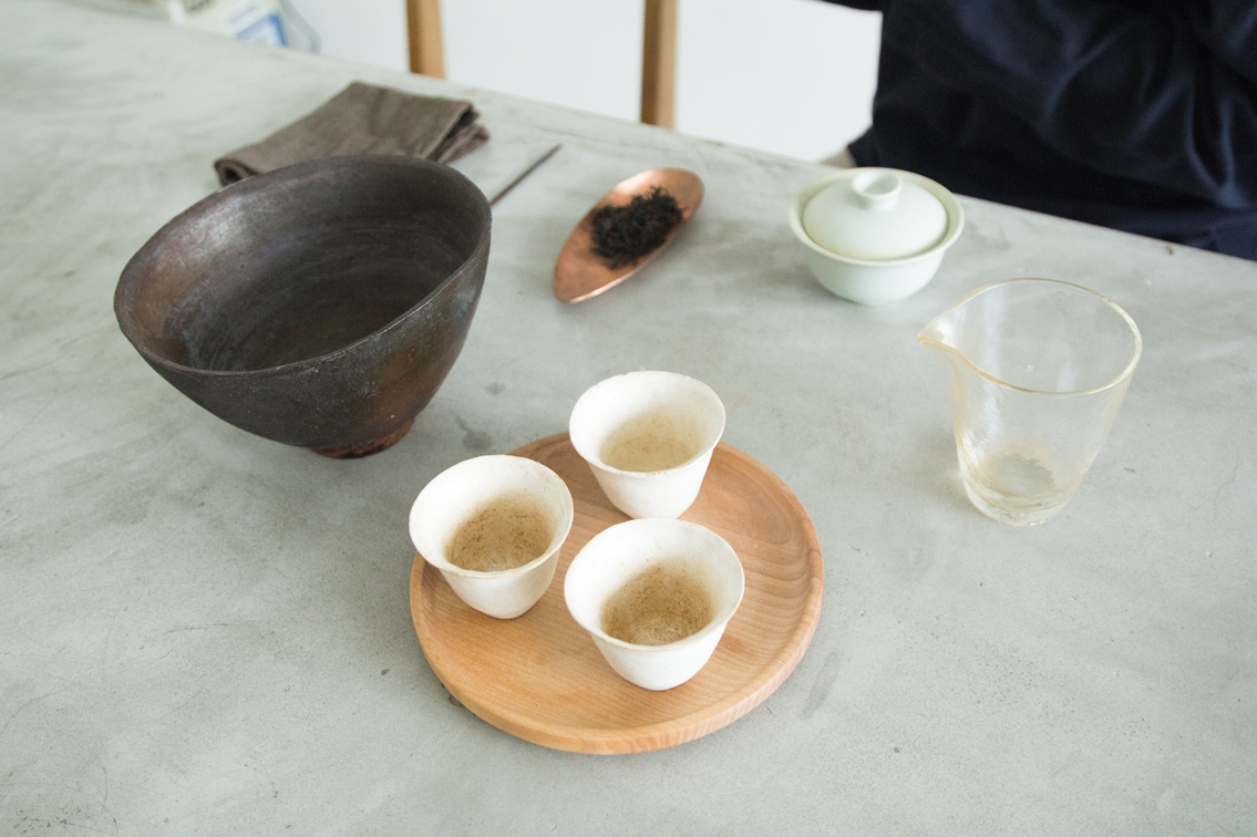 A comprehensive set for the Gong Fu Pao (Kungfu Brew) – from left clockwise: a bowl for dispensing rinses, linen cloth, stirrer, black tea leaves on a copper plate, the gaì wân (lid and bowl), serving glass, and three clay cups.