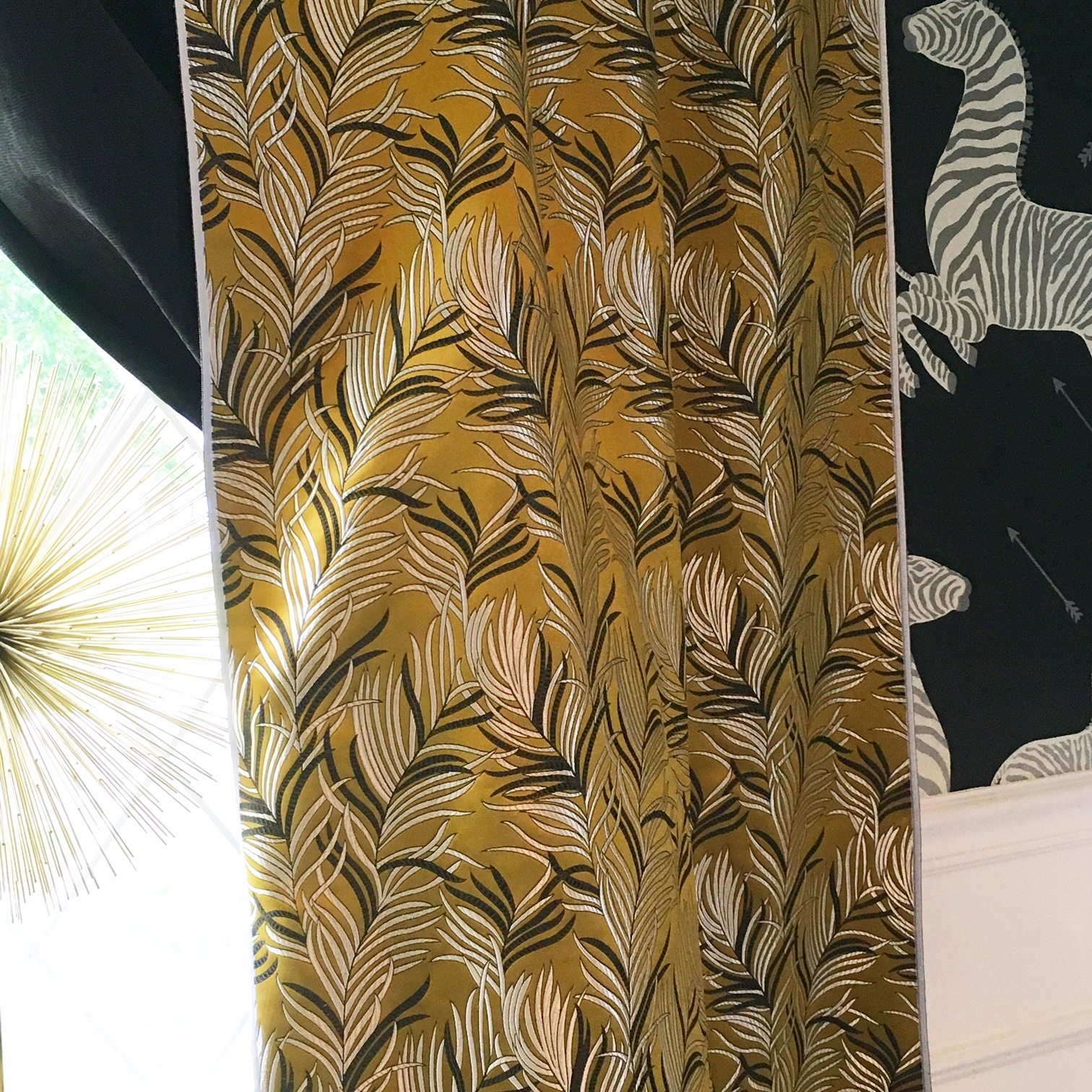 I loved the texture of the metal starburst, chartreuse brocade with metallic print curtains and the wallpaper with metallic finishes in the zebra's stripes.