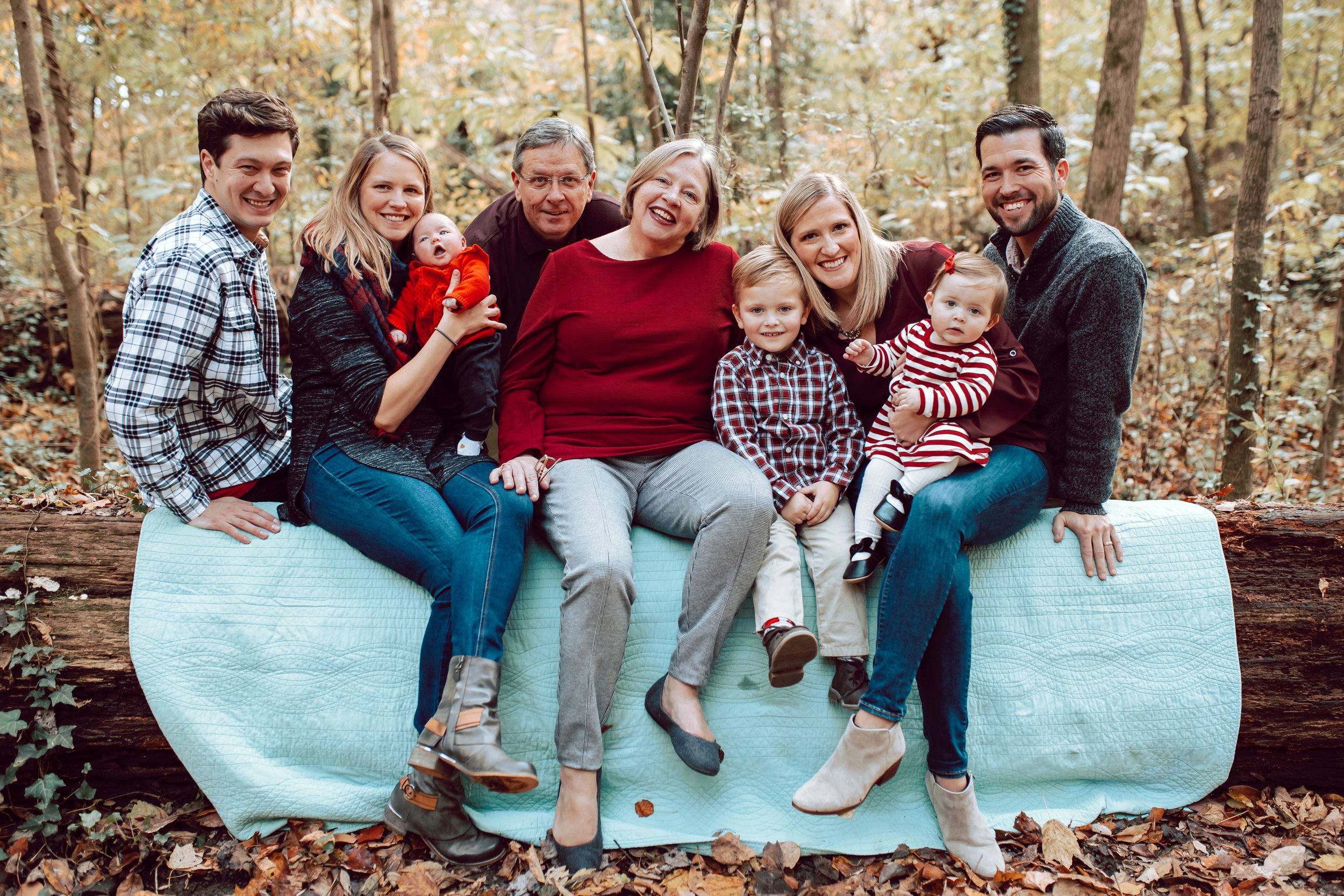 Family sits on a log in Overton Park in the fall.