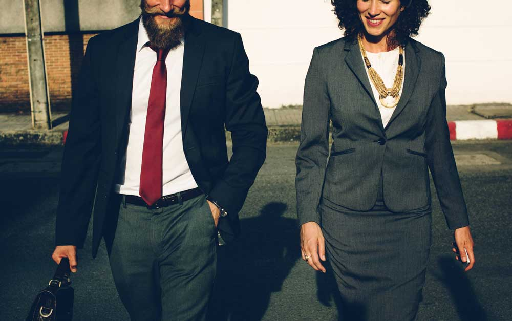 Man and woman walking out of a business meeting.