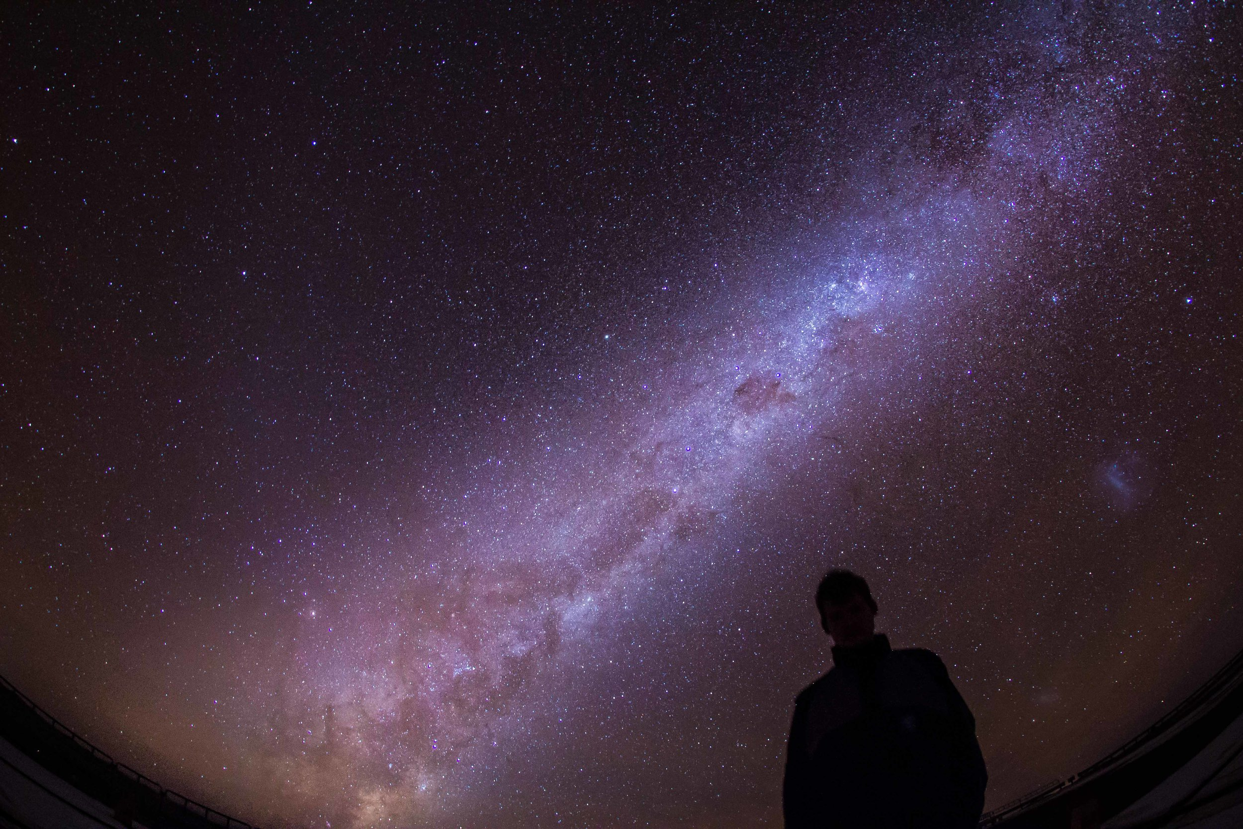 Me, with the Galactic center rising behind me. The  Magellanic Clouds  are clearly seen to my right.  © Dr. Grant Tremblay