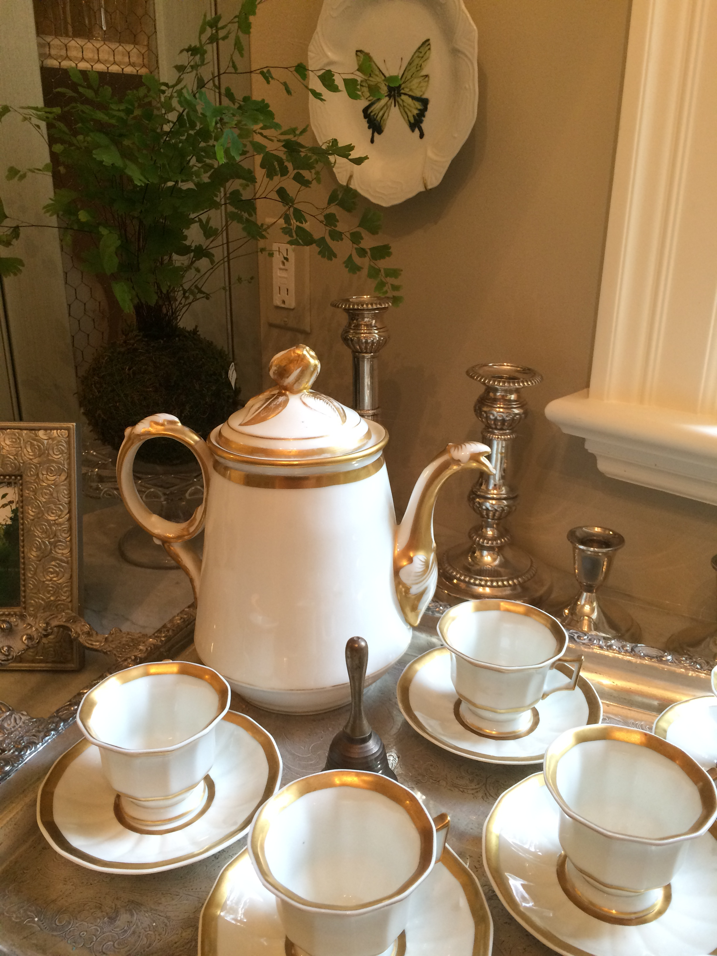 A tray of Limoge cups and a coffee pot, trayed up and ready to serve.