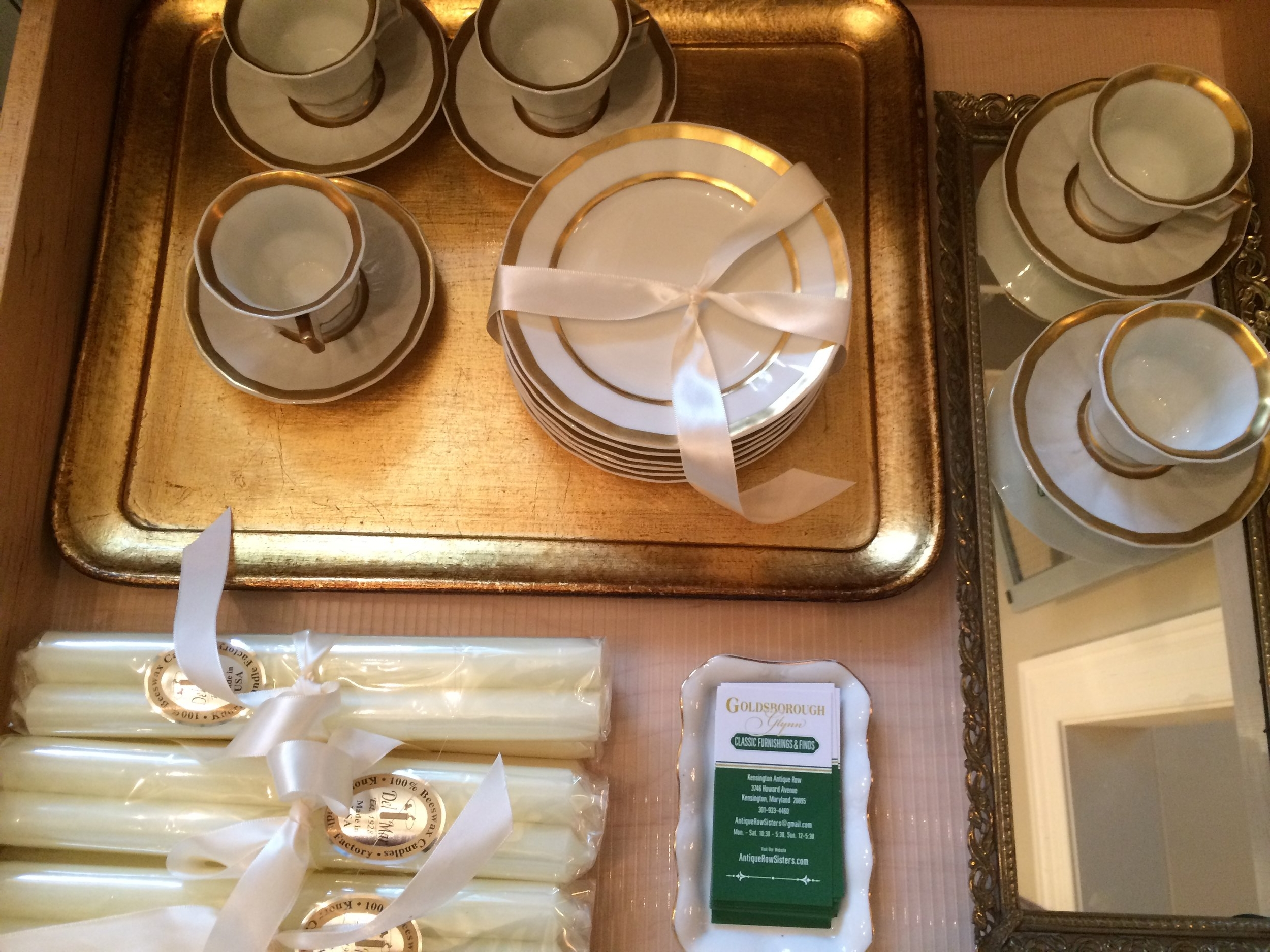 An ivory and gold drawer of limoge cups and saucers and Royal Cierge 100% bees wax candles sticks.