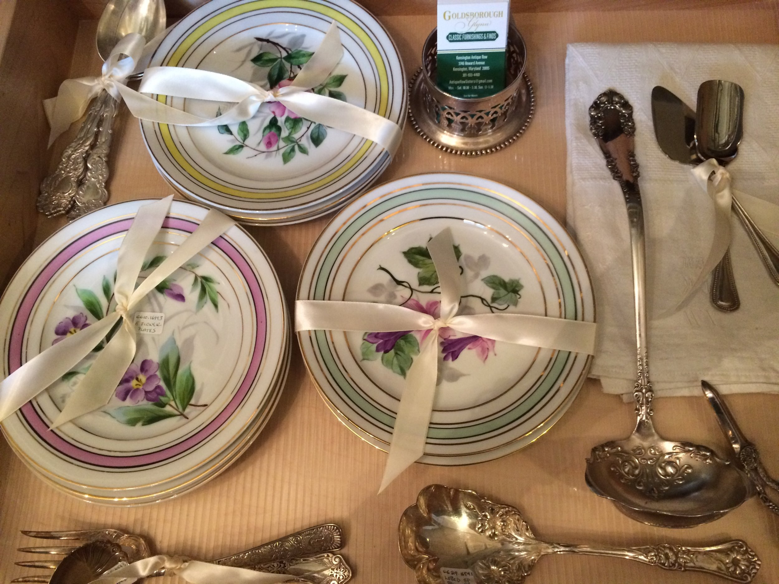 A drawer full of interesting fruit or dessert plates and assorted silver serving ware.