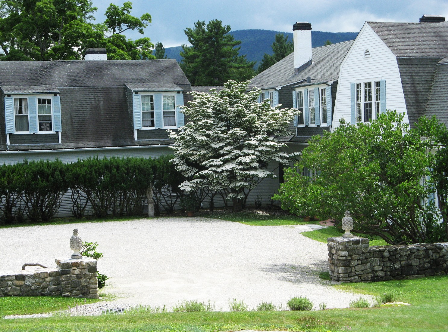 The Pebble Court is graced by a Kousa dogwood, yew hedge, trumpet vine and historic Hay statuary.