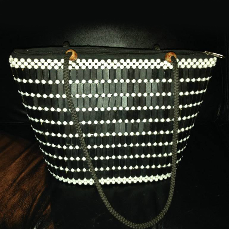 Handbag         $40.00 (Cash/Cheque) | $51.00 (Credit)  Handcrafted and unique in design. This handbag is decorated in wooden beads and features rope handles and a zipper enclosure.