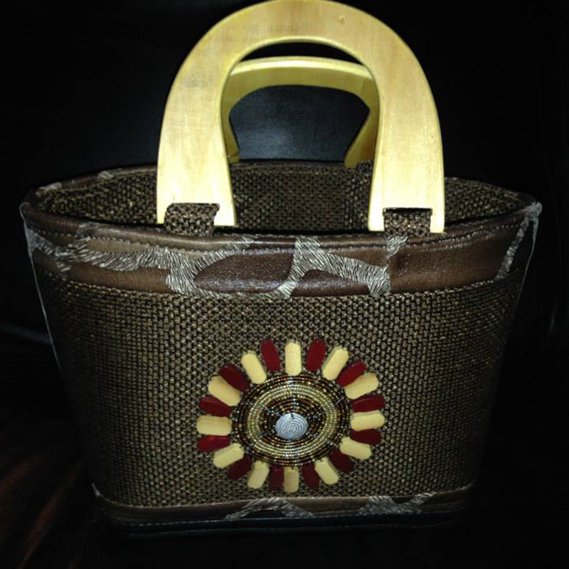 Handbag         $40.00 (Cash/Cheque) | $51.00 (Credit)   Handcrafted and unique in design. This handbag is intricately woven and features wooden handles and a beautiful beaded design.