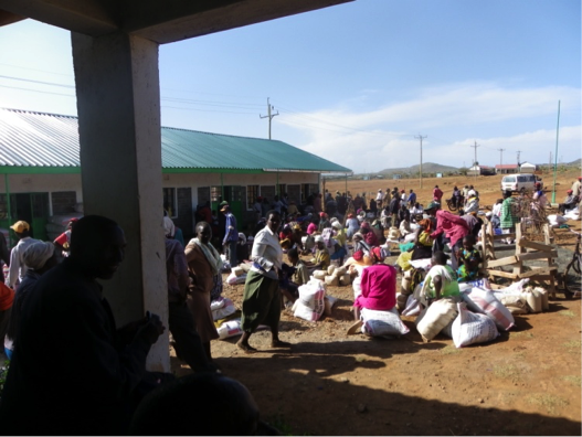 Families sitting on their bags of seed and fertilizer.