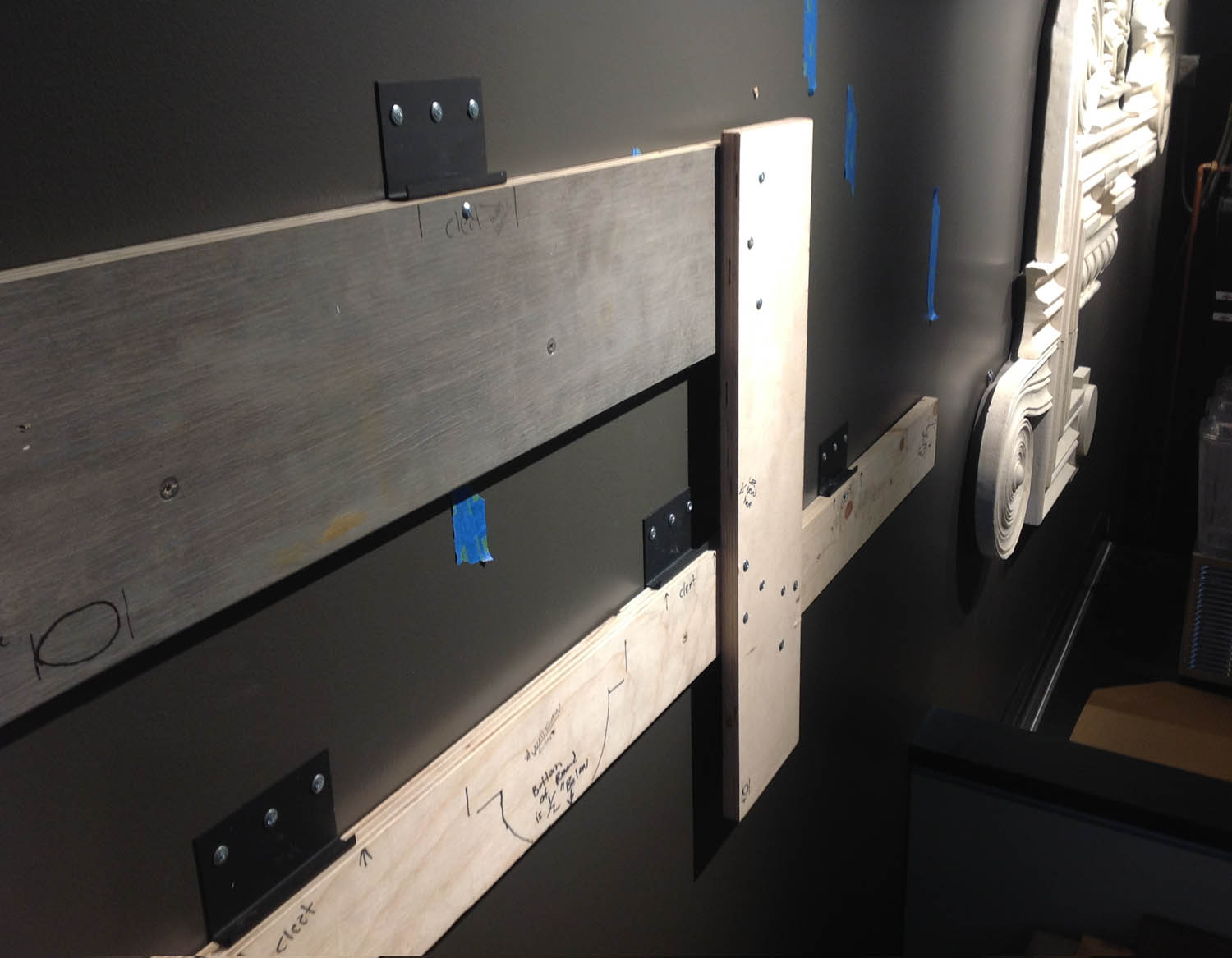 Installation templates were made for each cluster. The templates were temporarily screwed onto the wall during installation, and served to identify the exact position for each hidden metal cleat. The cleats locked into a slot that was previously made in the plywood backing. Cleats fabricated by  Bishop Metals