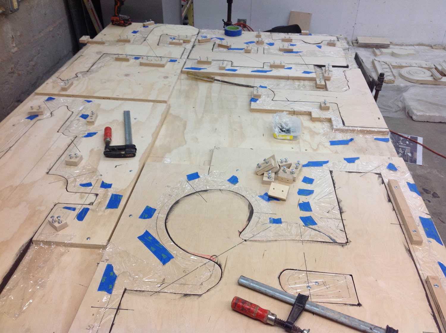 The parts needed to be glued down to a plywood backing. Each cluster was divided into sub-sections, to control for weight. A templating system was developed (consultation provided by artist Matthew Clifford) to keep all the parts aligned while glueing them down.