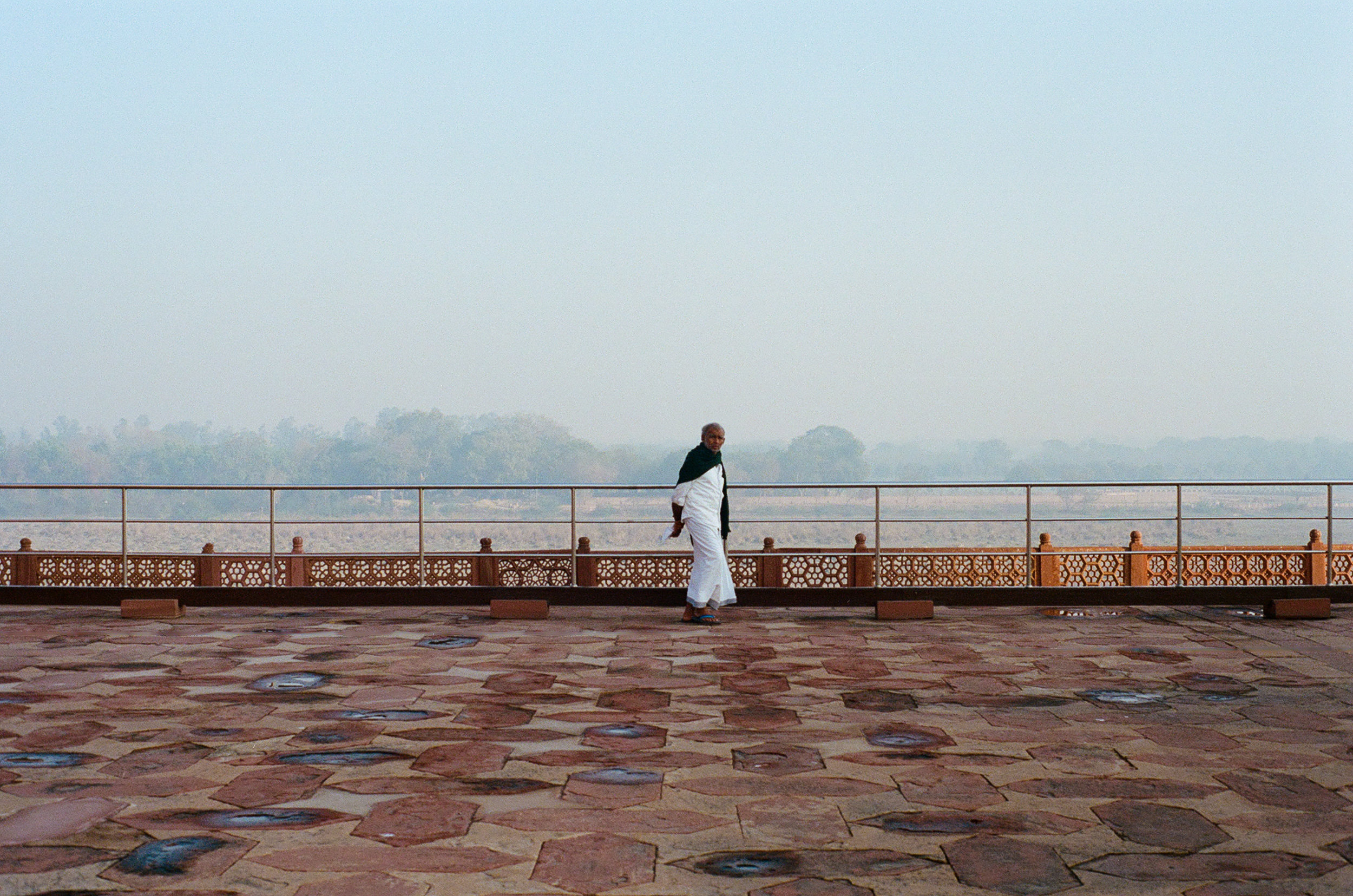 One really effective usage of negative space is to show solitude. Here the man is dwarfed by the empty spaces to all sides of him. Despite being taken at the busy Taj Mahal, the emptiness makes the environment feel calm.