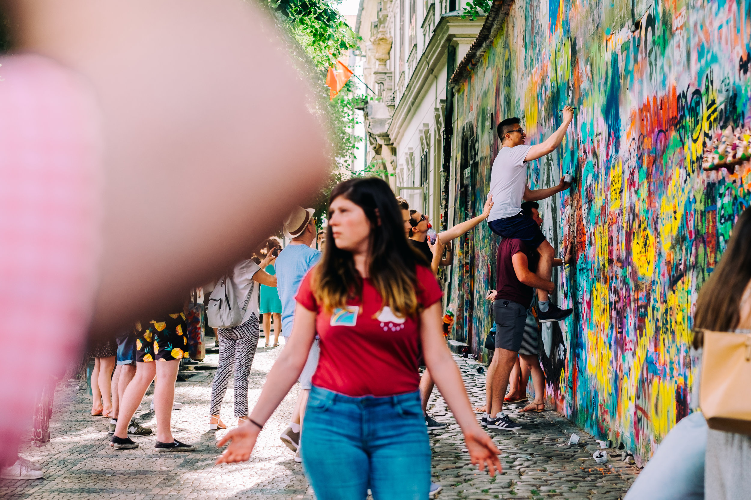 The intent of this image was to show the chaos of the John Lennon Wall in Prague, but also bring attention to the men in the back. But creating a foreground with the man's elbow, and a mid-ground with the woman in read, The Eye is slowly drawn to the men at the wall while giving the viewer a sense of crowding.