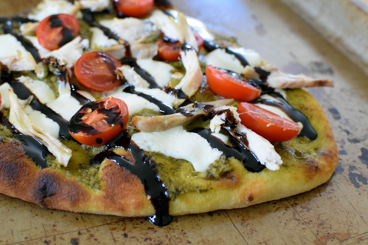 Pesto Caprese Pizza is summer in pizza form - with balsamic drizzle, of course. Ready in 15 minutes! | themillennialmenu.com